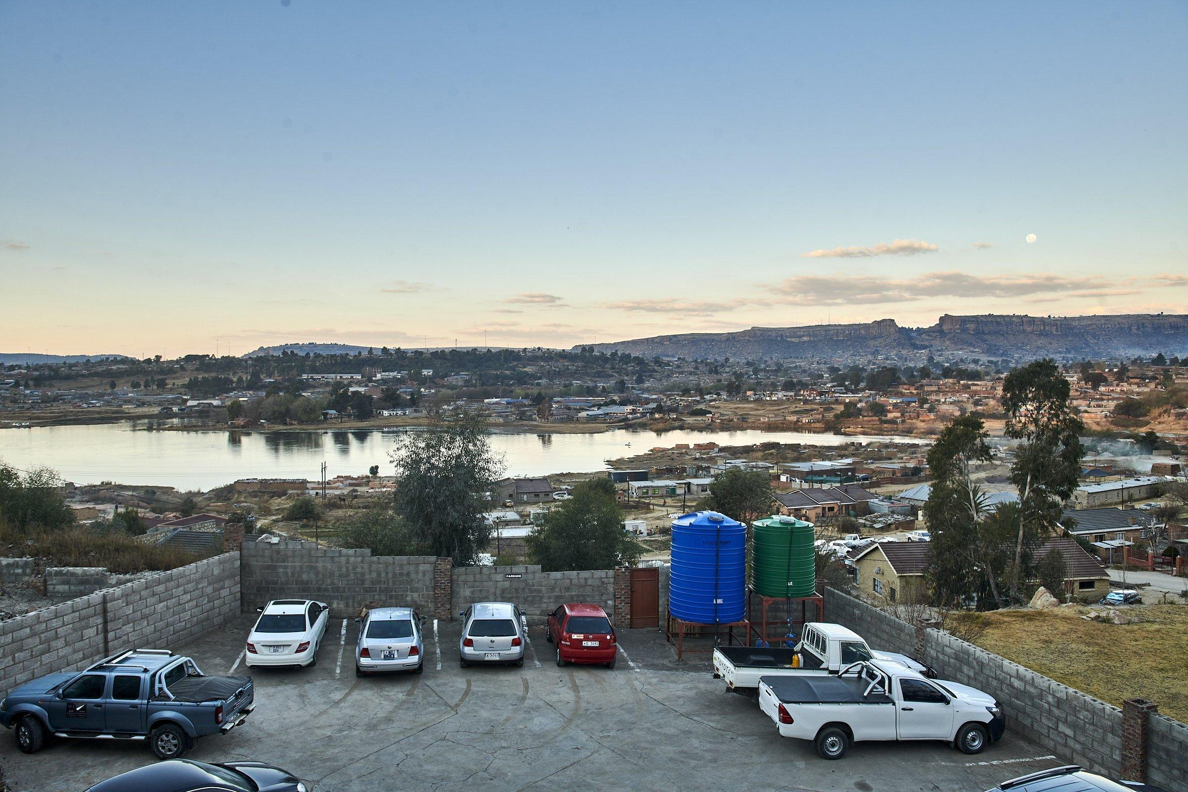 In der Hauptstadt Maseru liegt ein See hinter einem Parkplatz