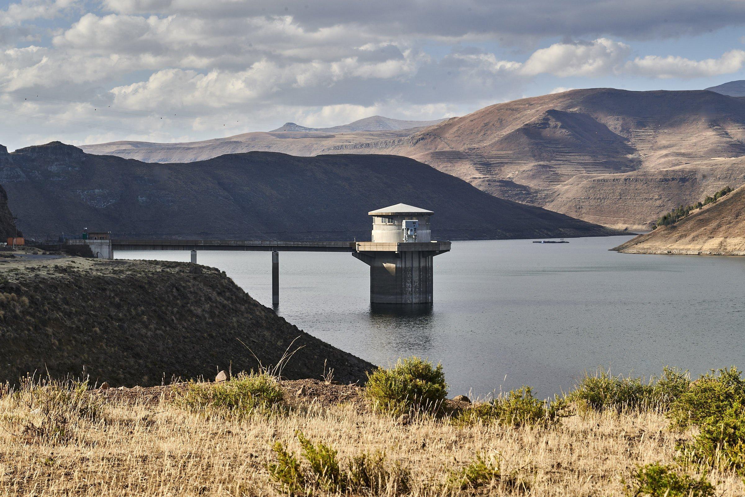 Auf dem Stausee  vor der Bergkulisse ragt ein Betonturm – die Pumpstation