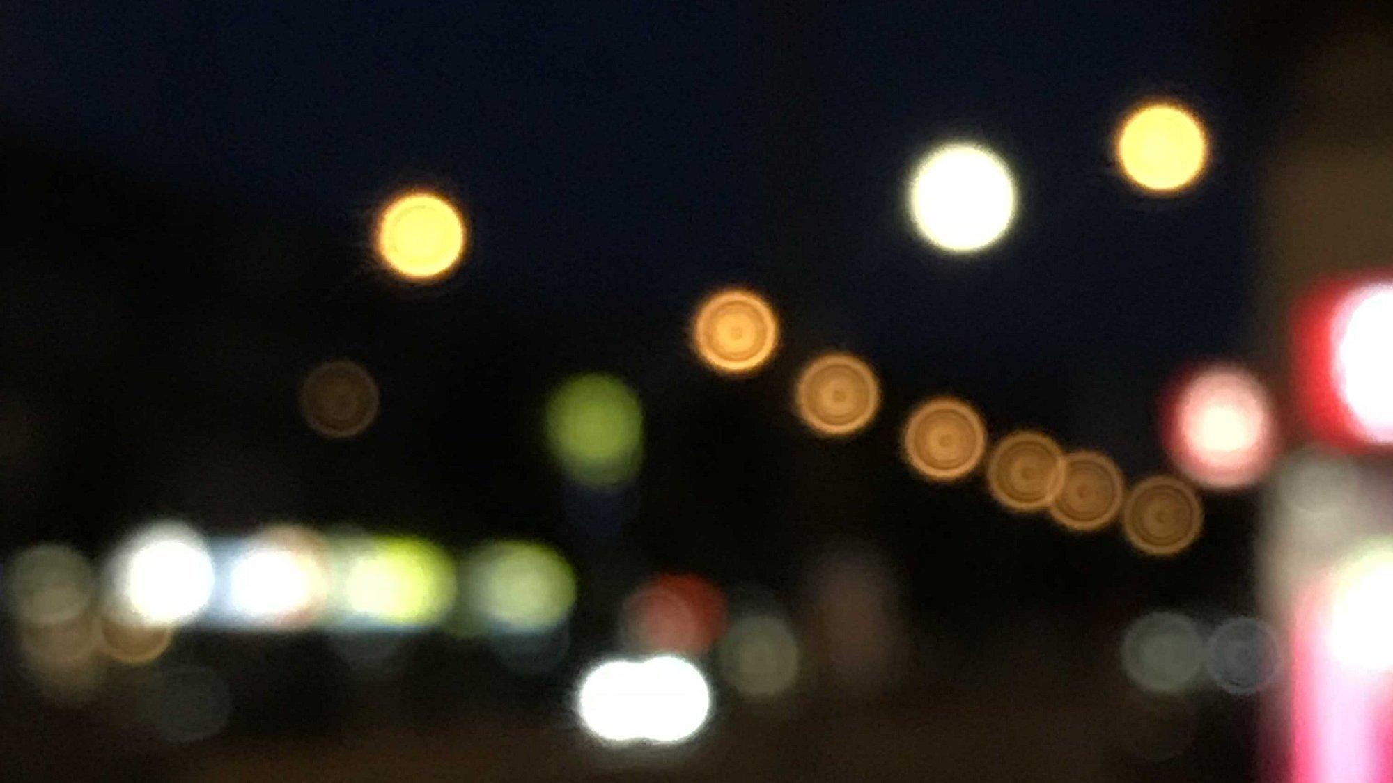 Es ist dunkel, man sieht lediglich das Leuchten von ein paar bunten unscharfen Lichtern