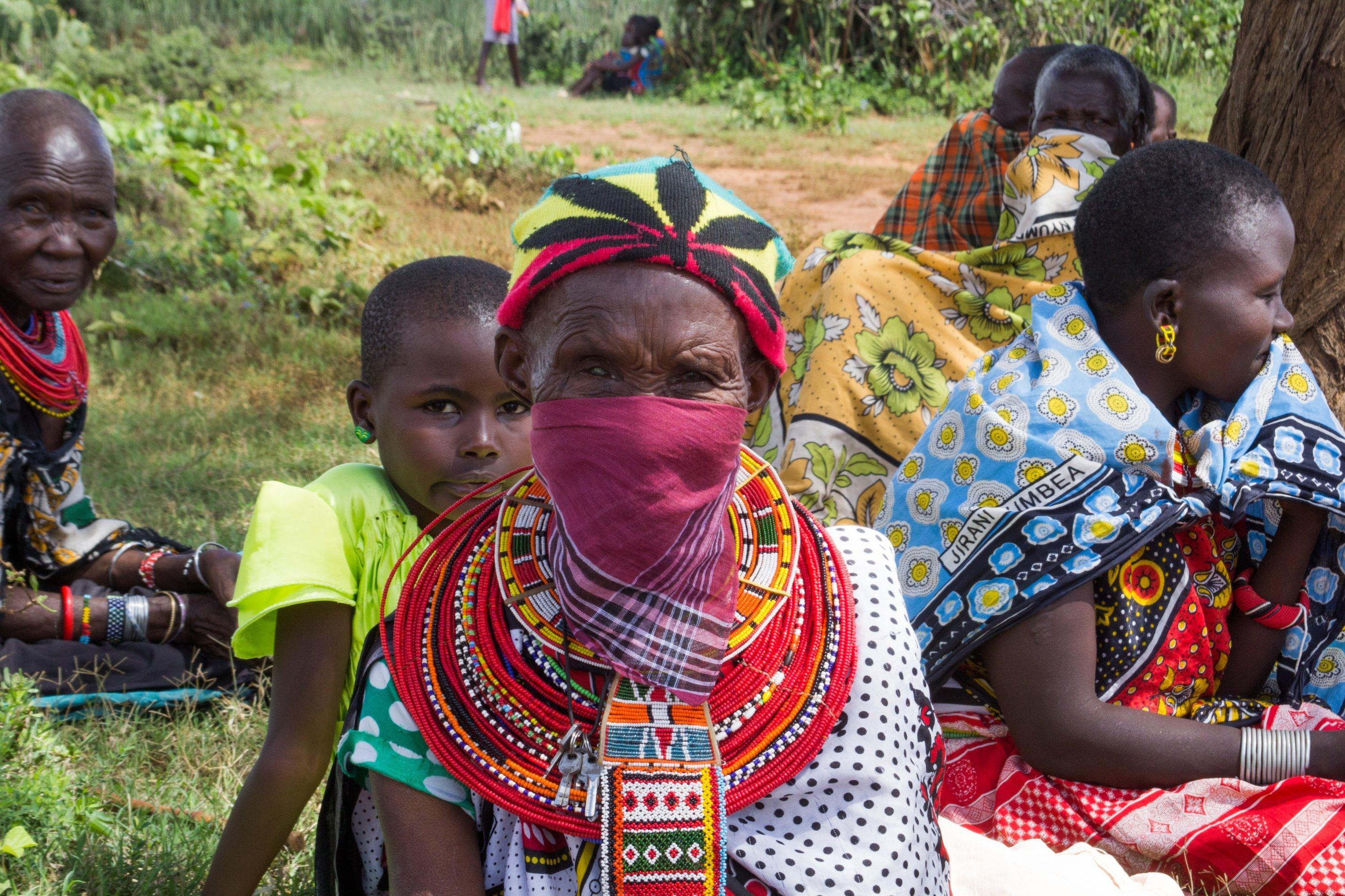 Einige Maasai-Frauen tragen mit Gesichtsmasken. Im Bild ist eine, die zu einer violetten Gesichtsmaske ein Kopftuch mit einer Cannabis-Pflanze trägt. Bisher gab es in der Region noch keine bekannten Infektionsfälle.