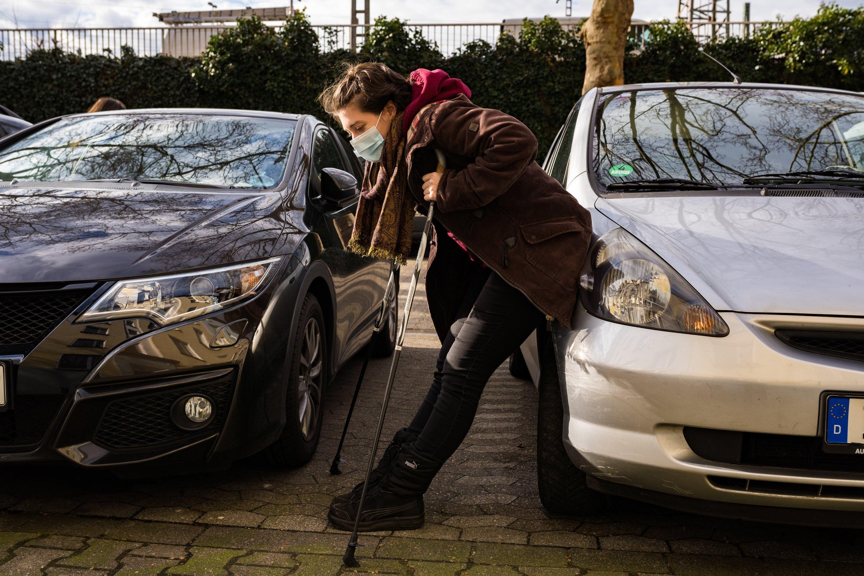 Luisa Meißner steht gebückt auf Krücken zwischen zwei Autos, und ruht sich aus. Sie hat eine Atemschutzmaske auf.