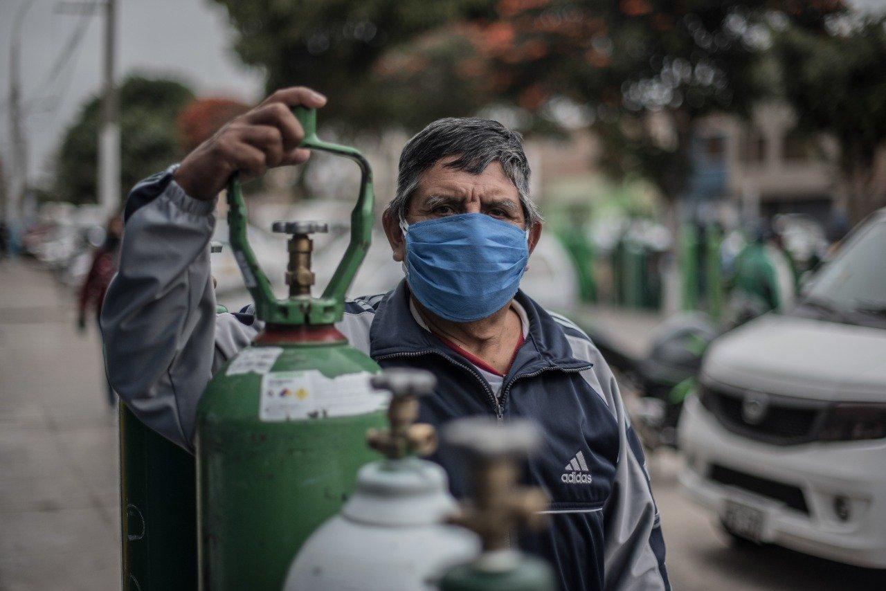 Im Vordergrund eine mannshohe grüne Sauerstoff-Flasche. Dahinter ein Mann mit grauen Haaren und buschigen grauen Augenbrauen. Der Mund ist mit einem blauen Mundschutz bedeckt.