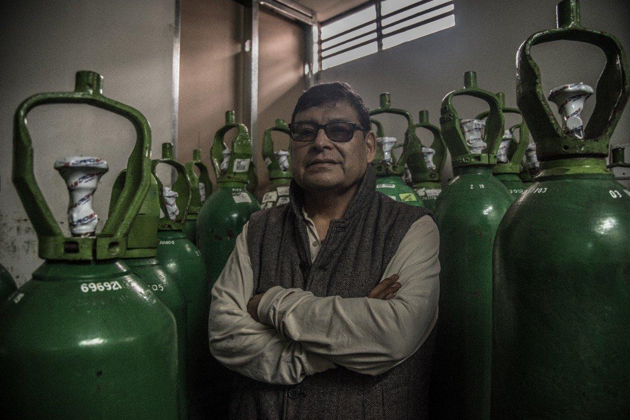 Rund 60-jähriger Mann mit Brille, verschränkten Armen, steht umgeben von grünen Sauerstoff-Flaschen aus Stahl.