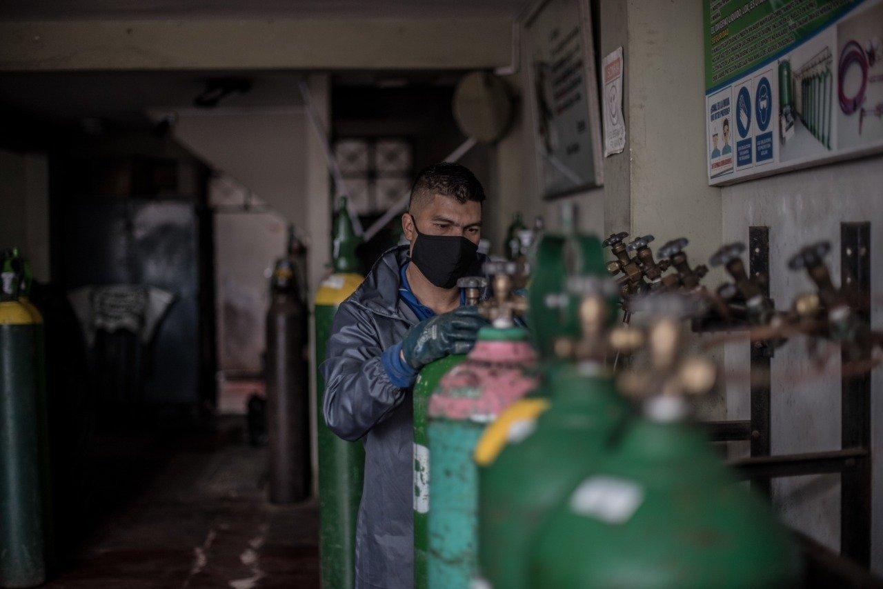 Grüne Sauerstoff-Flasche, dahinter ein Mechaniker mit Mundschutz.