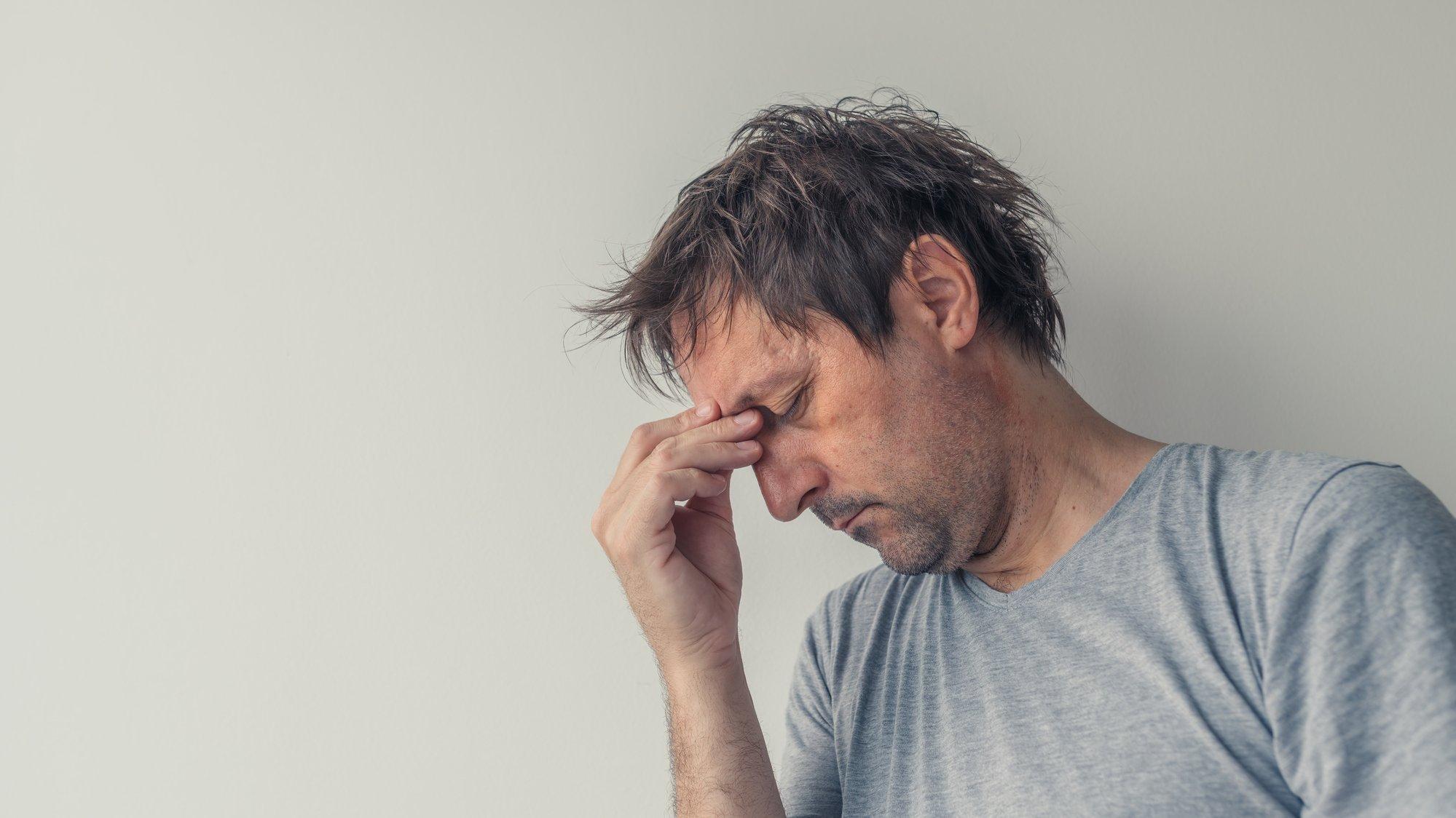 Ein Mann mittleren Alters fasst sich mit den Händen an die Stirn.