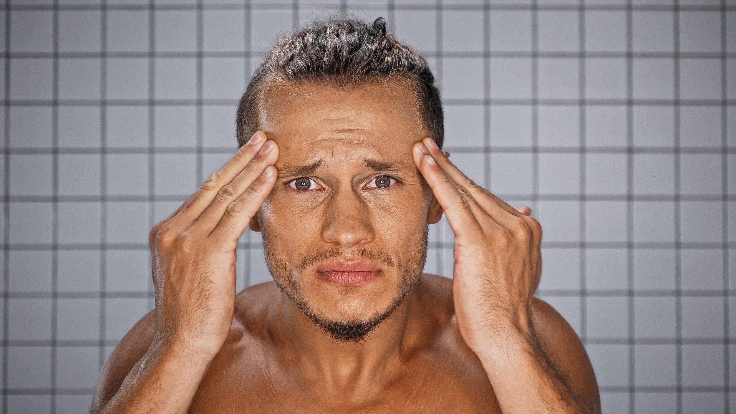 Ein mittelalter Mann betrachtet sorgenvoll sein Spiegelbild und prüft, ob neue Hautfalten hinzugekommen sind.