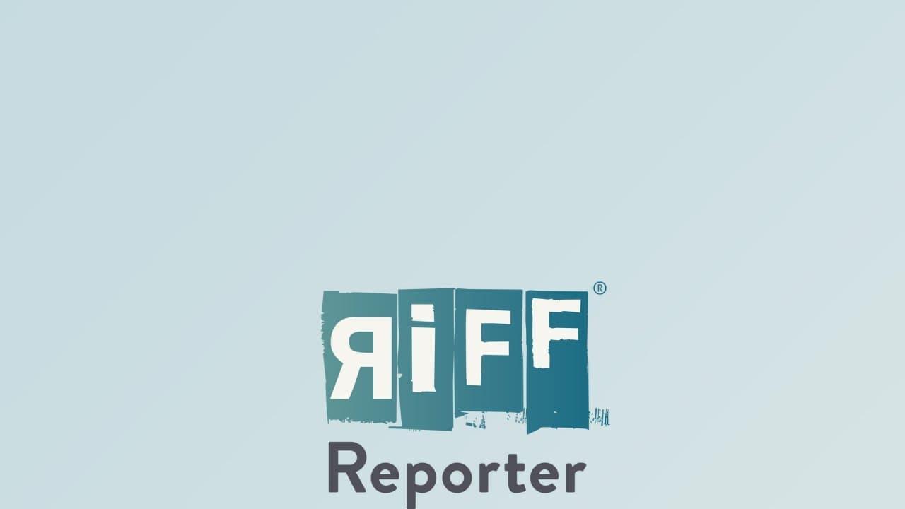 Eine junge Frau mit kurzen, roten Haaren lehnt an einer hellen Wand und wird von der Sonne beschienen. Sie trägt ein weißes Hemd, blaue Jeans und guckt selbstsicher in die Kamera.