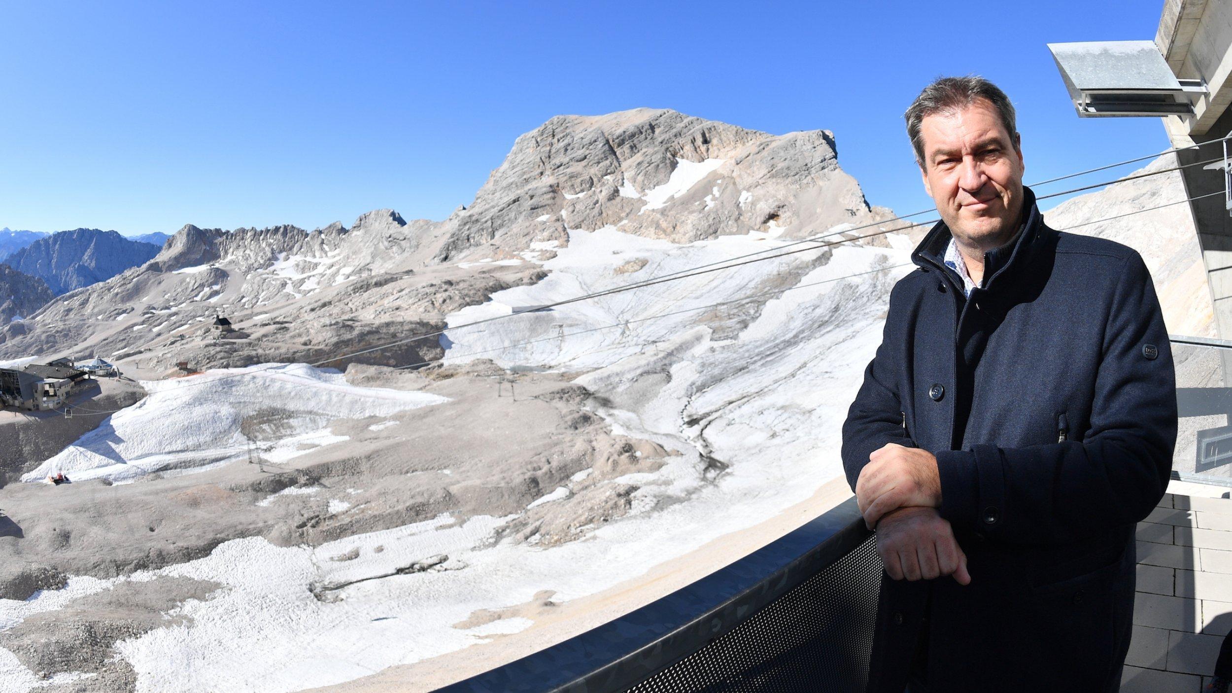 Markus Söder, CSU-Vorsitzender und bayerischer Ministerpräsident, steht rechts im Bild am Geländer eines Balkons und blickt in die Kamera. Hinter und unter ihm ist das Zugspitzplateau mit spärlichem Eis zu sehen. Aufgenommen bei einer Klimatour Anfang September auf der Zugspitze.