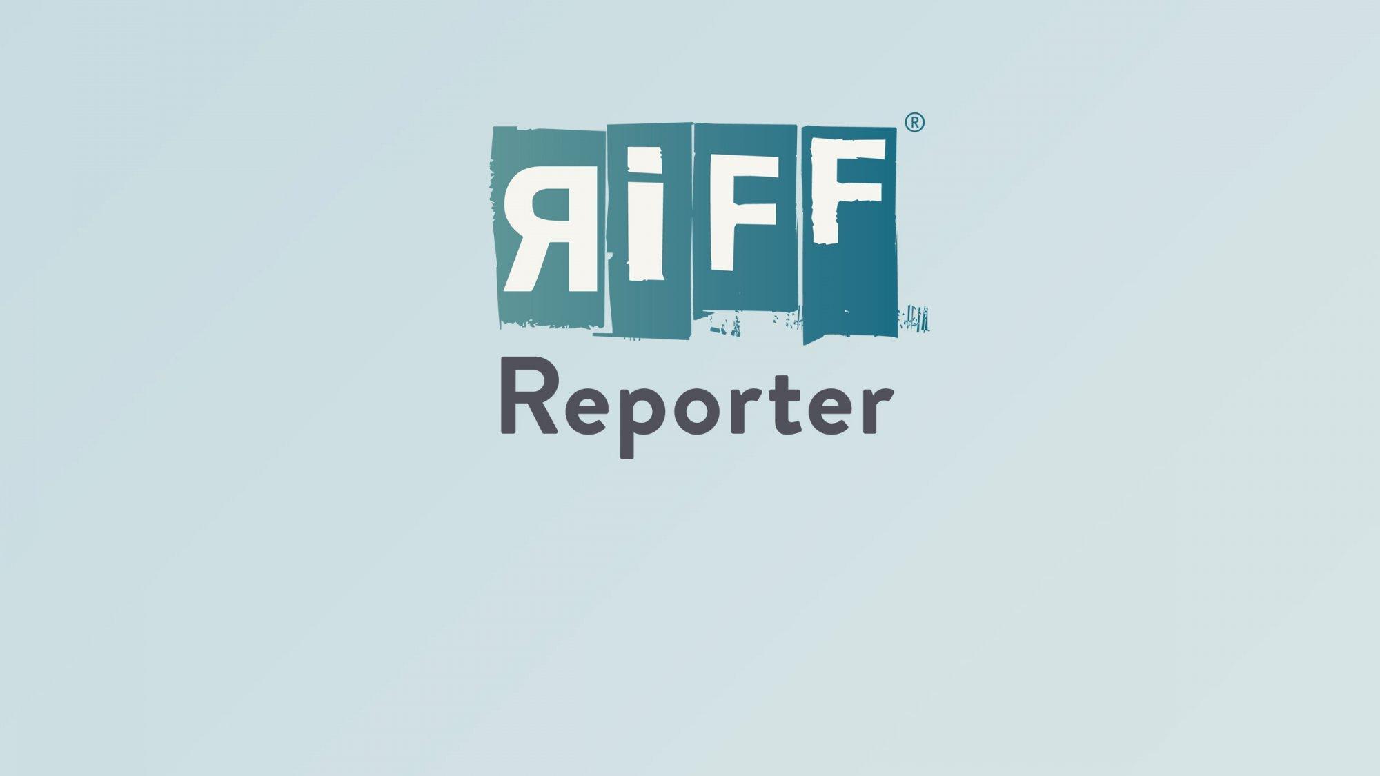Ein blaues Rad liegt am Ufer eines Sees.