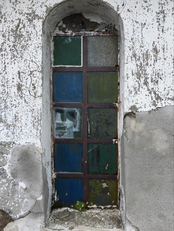 verschiedenfarbige Glaseinsätze zwischen weißen Kalkwänden.