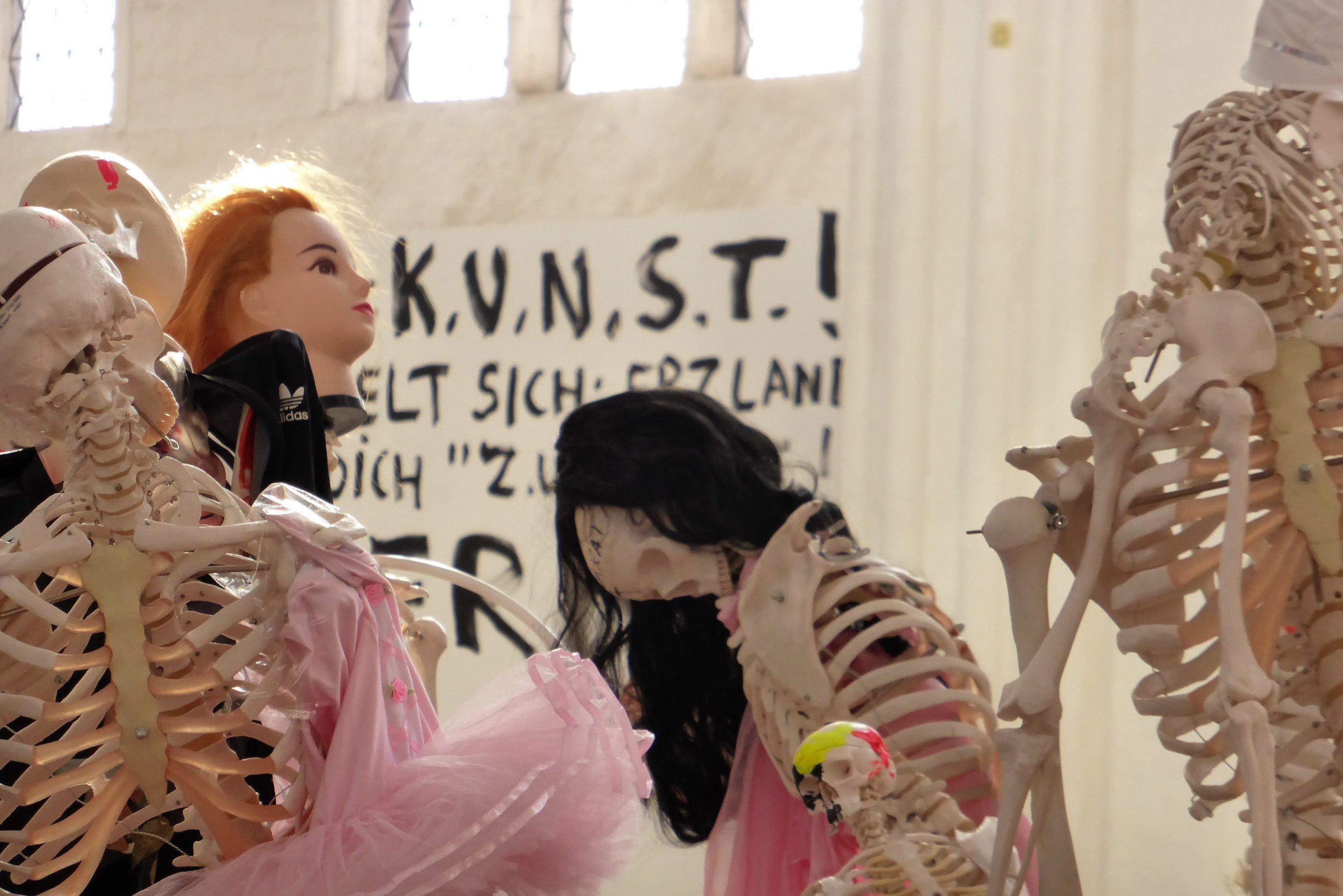 Detail der Meese-Installation: Puppenartig verfremdete Skelette stehen vor einem Wandplakat mit der Aufschrift KUNST!