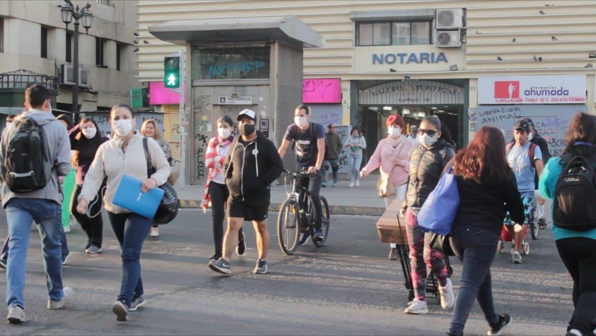 Menschen mit Mundschutzmasken auf einer Straße in Santiago.