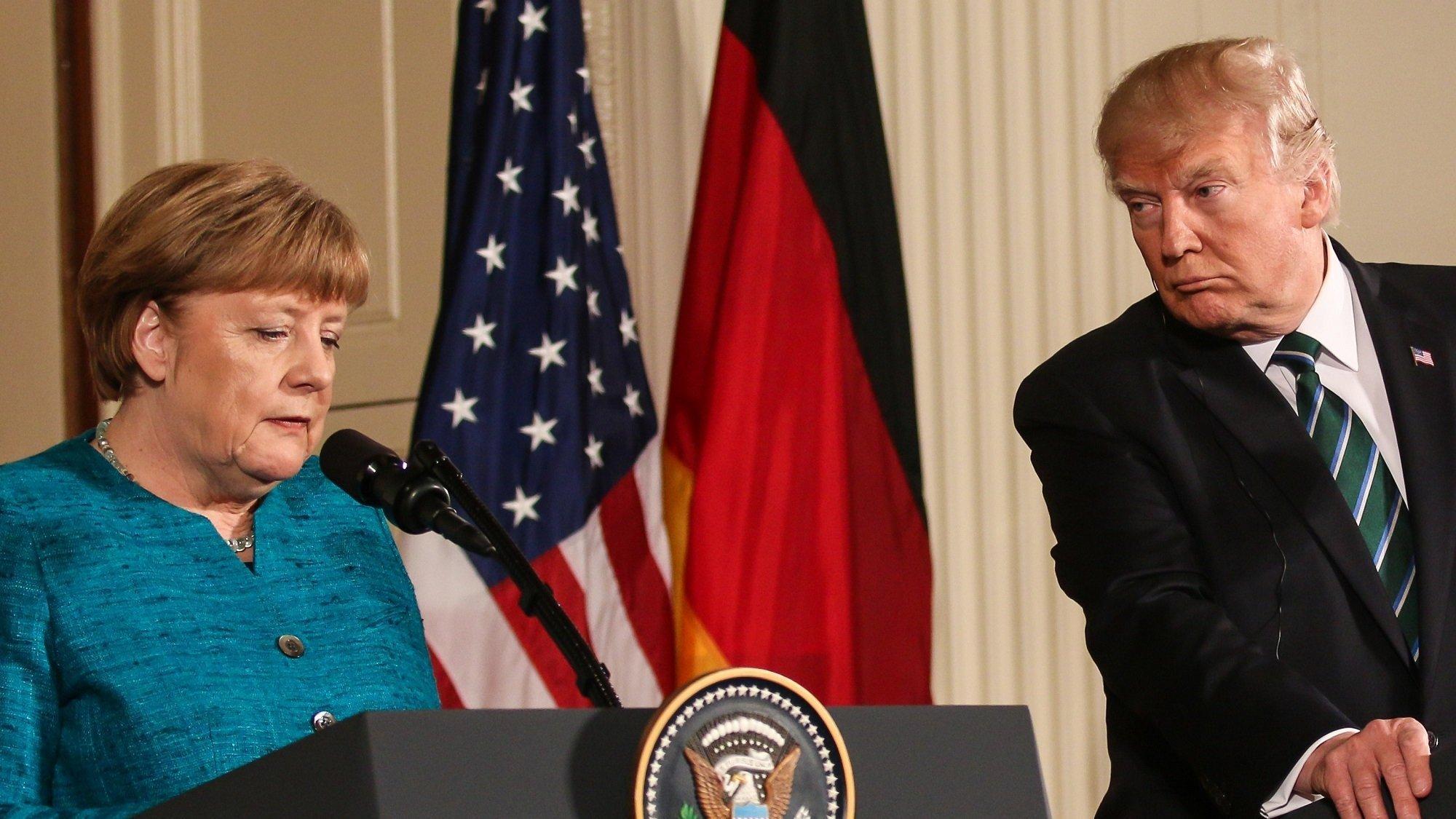 Angela Merkel und Donald Trump stehen nebeneinander bei einer Pressekonferenz. Trump schaut Merkel skeptisch an.