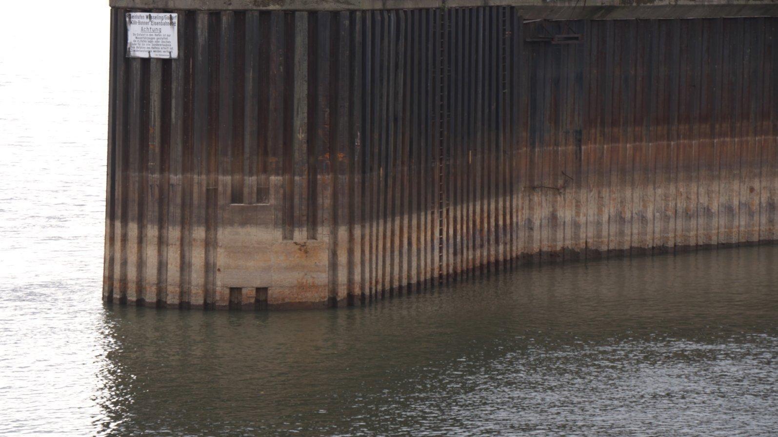 Braune Spundwand rechts von einem Fluss und links von einer Hafeneinfahrt mit Niedrigwasser.