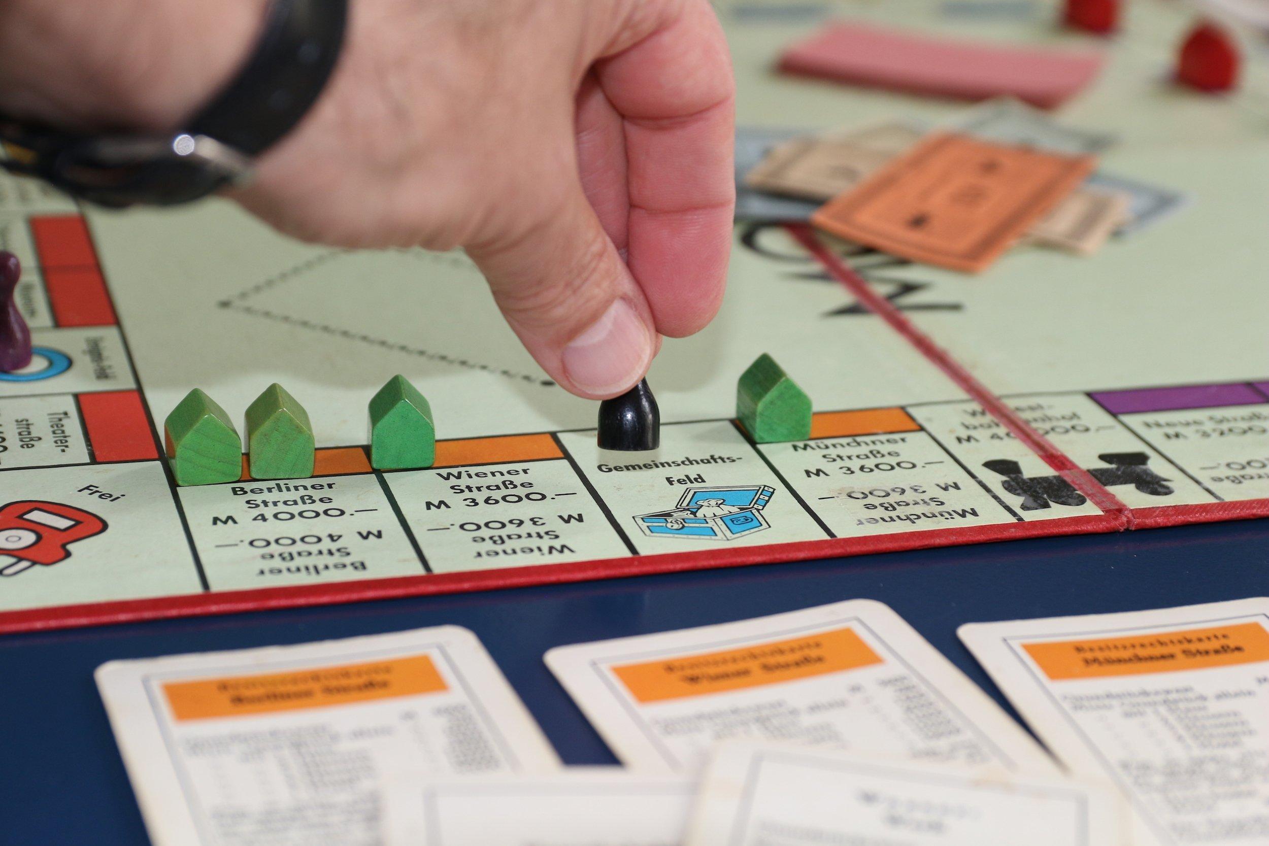 """Spielsituation bei Monopoly: Die schwarze Figur wird gerade von einer Hand auf dem Gemeinschafts-Feld zwischen Münchner und Wiener Straße abgestellt. Im Hintergrund liegt ein Stapel Geld in der Mitte. – Monopoly gilt als Spiel des Kapitalismus, dabei hatte sein erster Vorläufer """"The Landlord's Game"""" auch einen Satz Regeln für eine Gemeinwohl-Ökonomie. Damals konnten die Spieler umschalten, und dann wurden alle Mieten für Grundstücke – aber nicht die Anteile für Häuser – in der Mitte gesammelt. Wenn genug zusammengekommen war, mussten die Eigentümer von Elektrizitätswerk, der damals vorhandenen Straßenbahn und den Bahnhöfen ihre Karten an die Gemeinschaft verkaufen. Heute könnte man es so spielen, dass der Topf in der Mitte aufgeteilt wird, wenn eine Figur auf dem Gemeinschafts-Feld landet."""