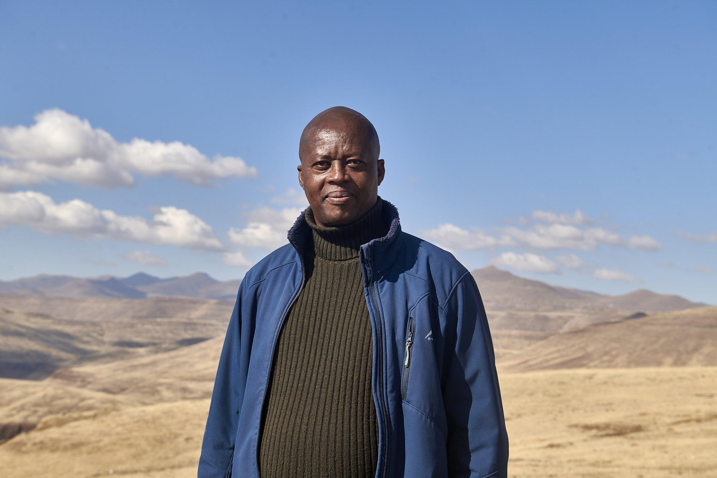 Seqhee steht vor der Berglandschaft, er trägt einen Rollkragen-Pullover, eine blaue Jacke und schaut in die Kamera