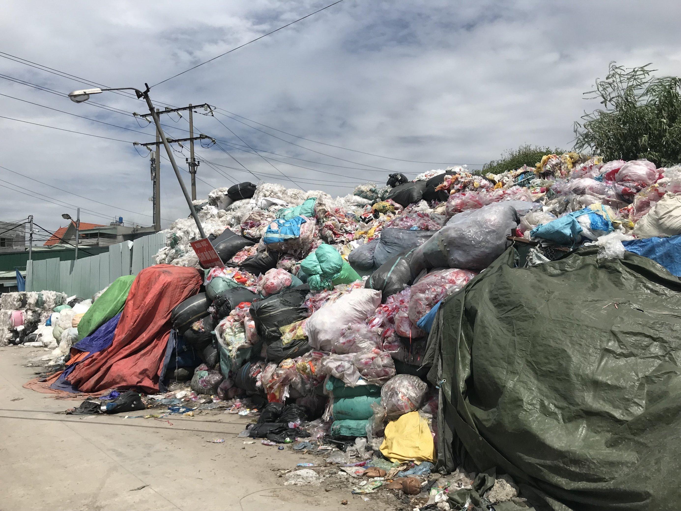 Ein Müllberg an einer Straße. Im Hintergrund sind Strommasten und eine Laterne zu erkennen.