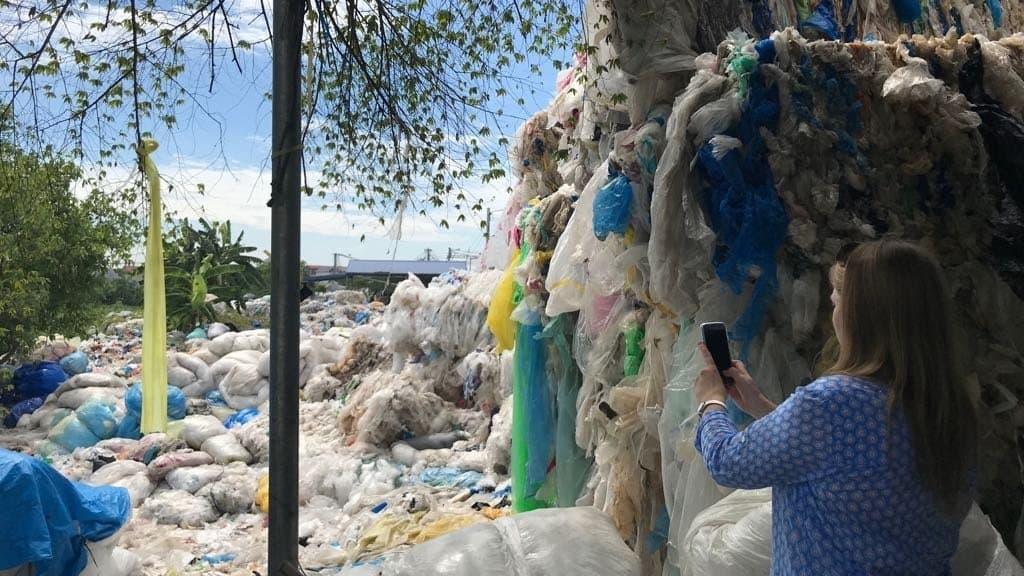 Jenna Jambeck steht mit dem Rücken zur Kamera und fotografiert mit einem Smartphone große Haufen Plastikmüll.