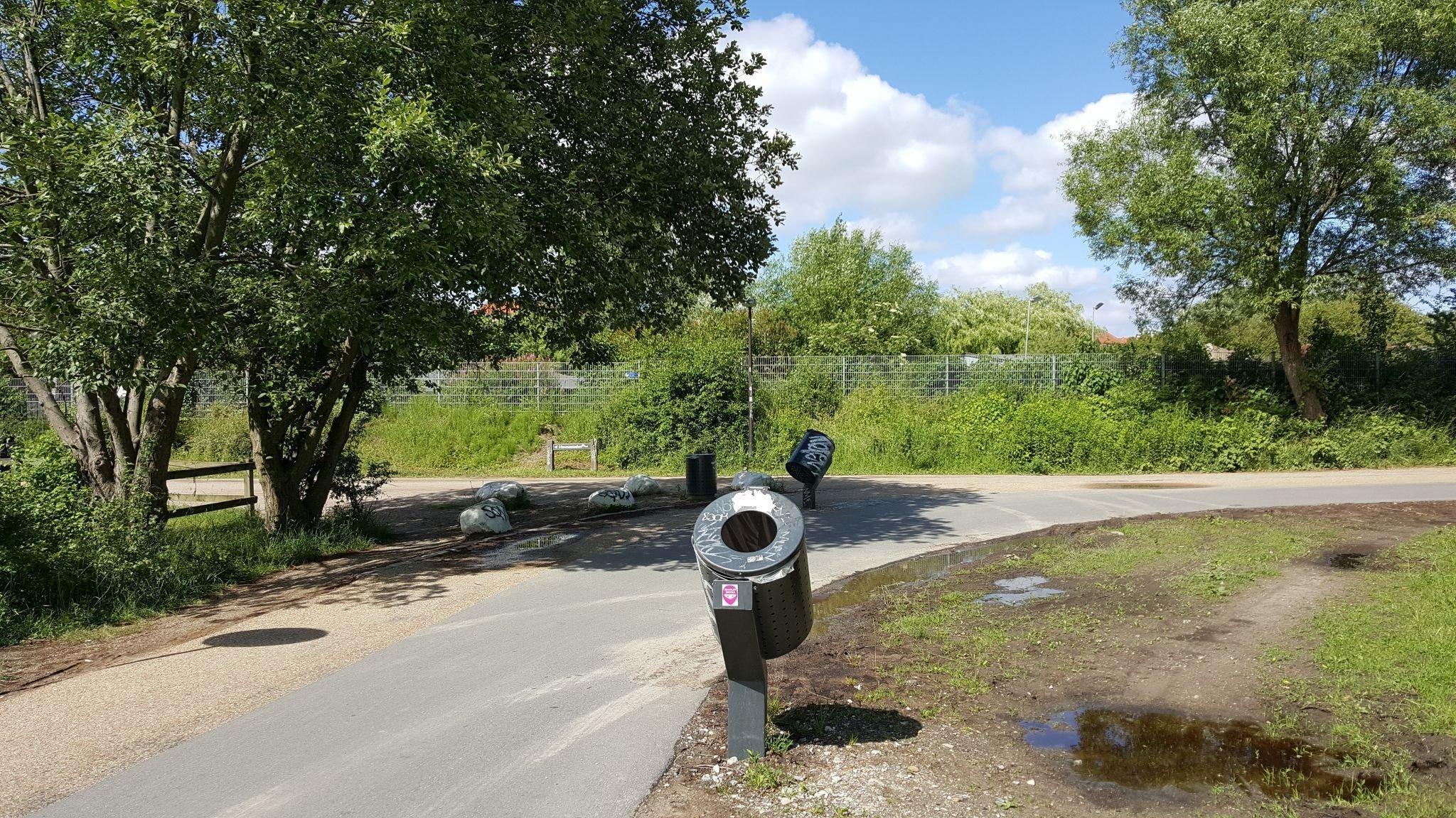 Radweg mit schrägem Mülleimer, in den man während der Radfahrt bequem Abfall entsorgen kann.