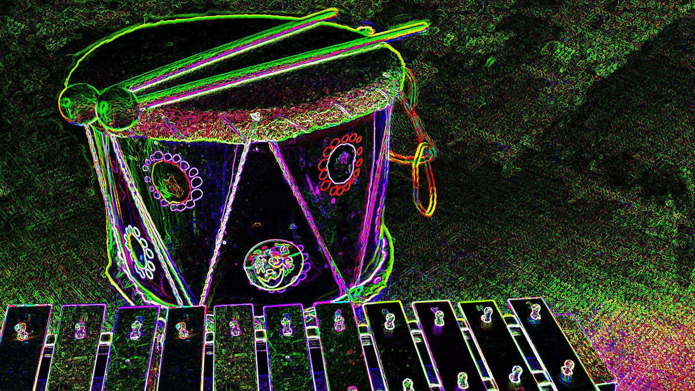 Stark verfremdete Aufnahme einer Trommel zusammen mit einem Glockenspiel. Ein Filter hat die Konturen auf dem Bild wie mit vielfarbigem Neonlicht verstärkt. Text dazu: Die Grundzüge von Rhythmus und Melodie lassen sich auch schon mit einfachen Instrumenten spielen.