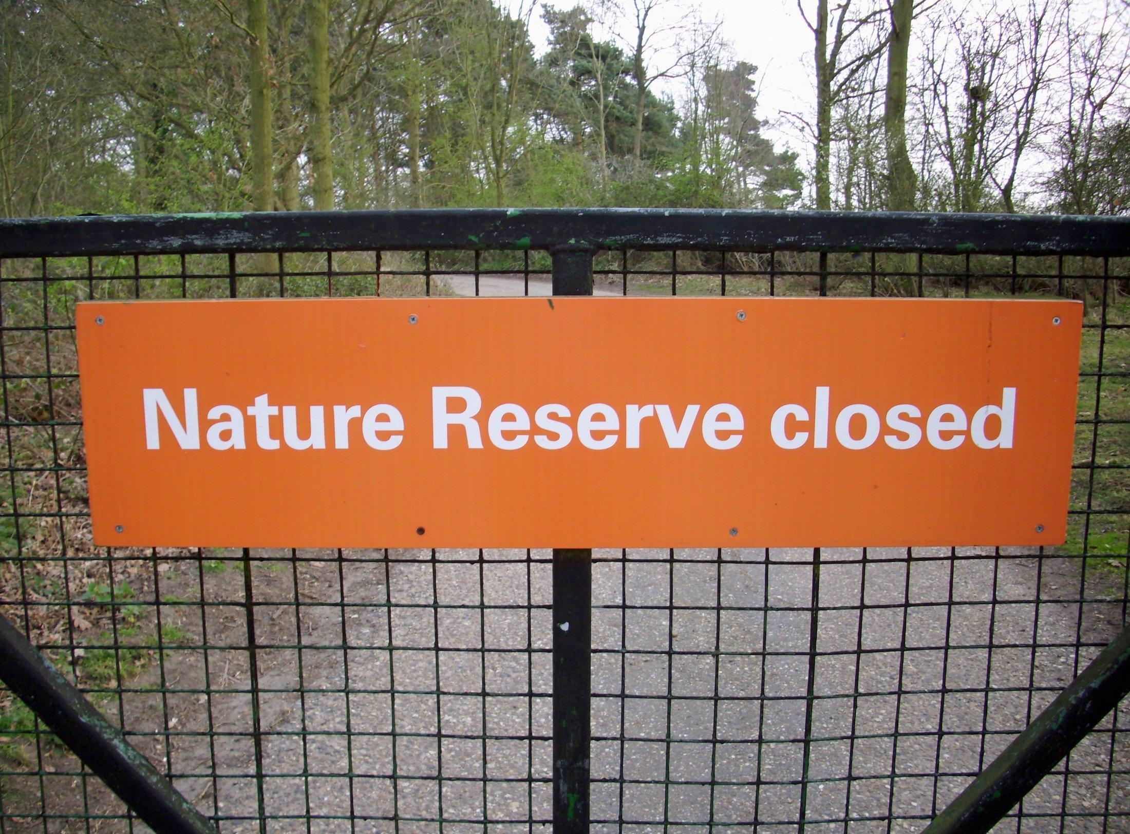 """Das Bild zeigt ein Schild mit der Aufschrift """"Nature Reserve Closed"""" an einem Metallzaun vor einem Wald."""