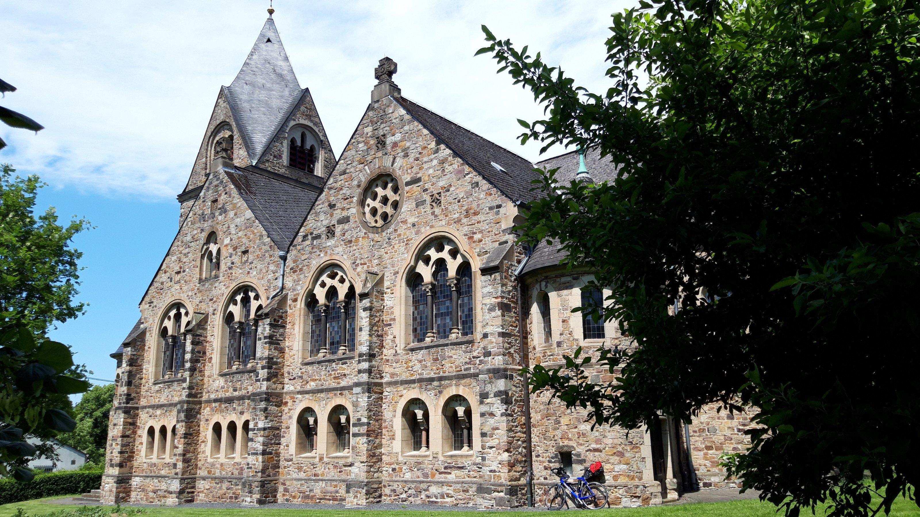 Das Vehikel des RadelndenReporters lehnt an der Evangelischen Pfarrkirche Dierdorf, eine neuromanische Staffelkirche aus den Jahren 1903bis 1904mit spätromanischem Westturm.