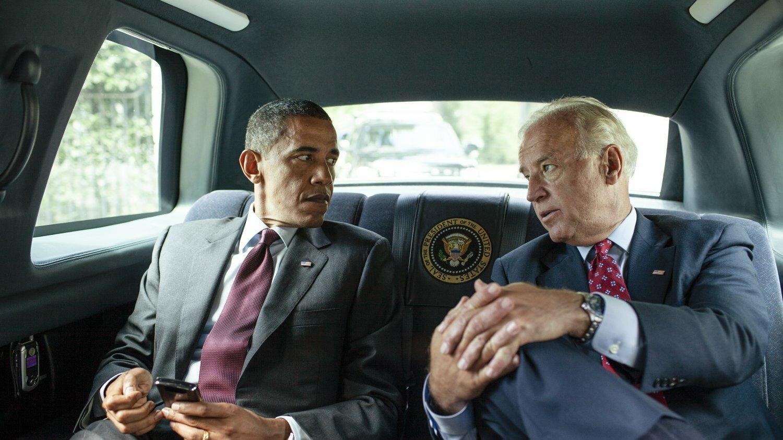 Zwei Männer im Anzug sitzen auf der Rückbank eines Autos