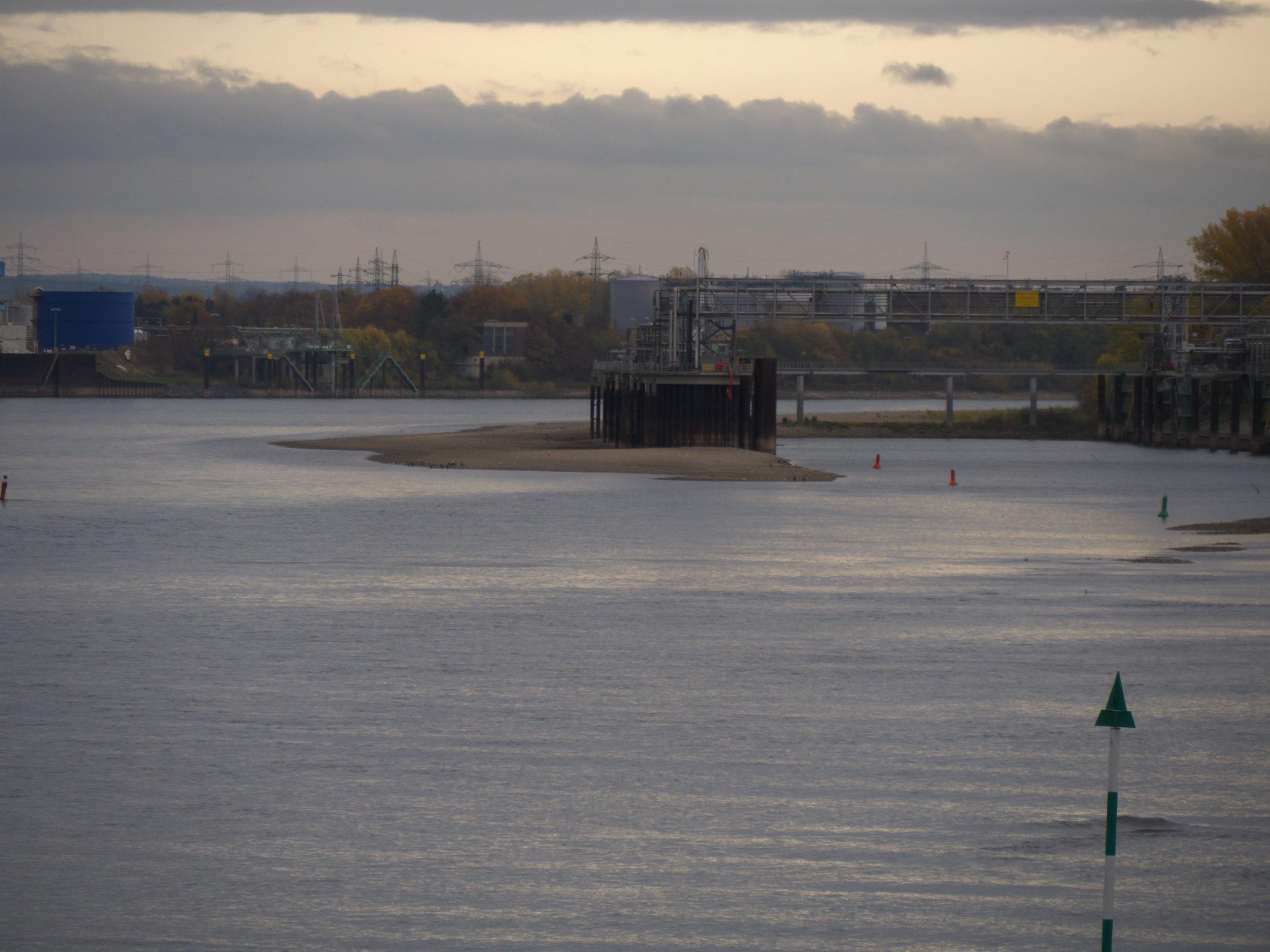 Hafenmole mit vielen Rohrleitungen steht frei auf einer Kiesbak in einem Fluss. In Hintergrund sind der Fluss, Strommasten, große Tanks und eine weitere Anlegestelle zu erkennen.