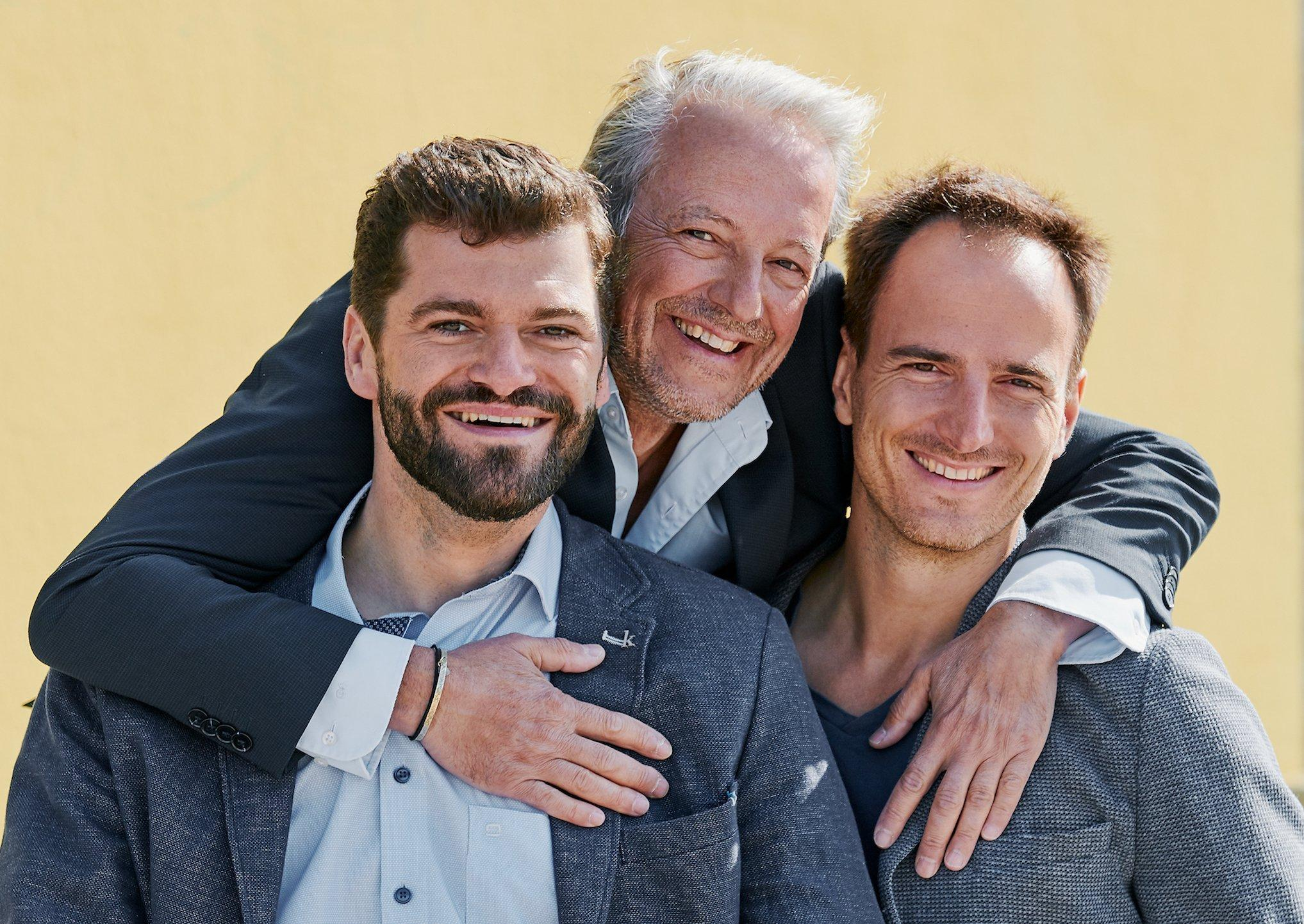 Murat Günak steht in der Mitte und legt von hintent seine Arme über die Schulter von Philipp Kahle und Beres Seelbach. Seine Hände ruhen jeweils auf der Brust seiner beiden Mitgründer. Alle drei lachen offen und herzlich in die Kamera.