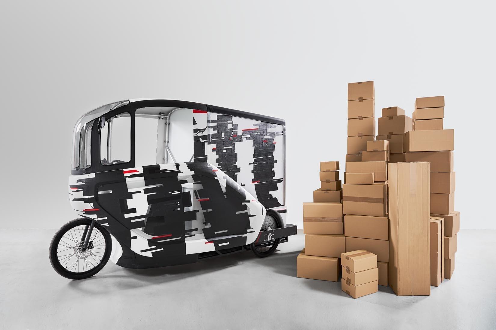 Neben dem schwarz-weiß-farbenem Lastenrad steht ein noch höherer Berg aus Paketen, die das Cargobike fassen kann.