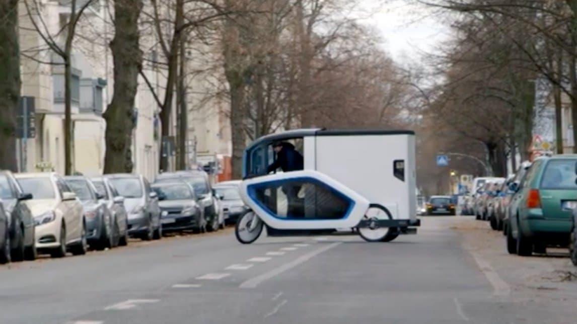 Die Ono ist ein Schwertransportern unter den Lastenrädern. Bei dem Wendemanöver mitten auf der Fahrbahn ist die Silhouette des weißen Gefährts mit der Fahrerkabine gut erkennbar. Mit ihrer Höhe von rund zwei Meter überragt sie die rechts und links parkenden Autos.