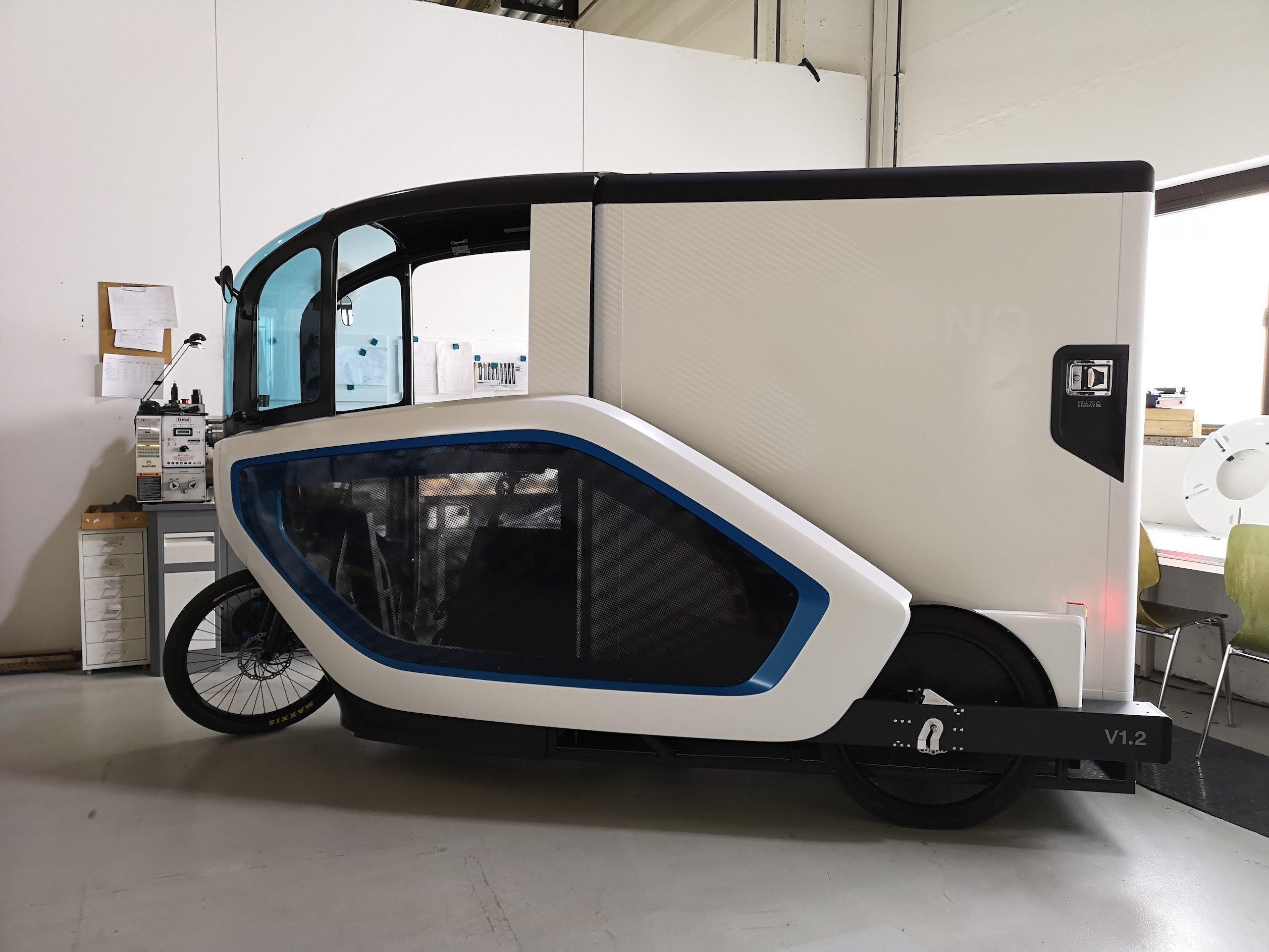 Das Lastenrad steht in der hellen Werkstatt, die gleichzeitig als Büro dient. Die Silhouette der Ono erinnert an einen kleinen Transporter, wirkt aber deutlich futuristischer. Das liegt an der aufgesetzten, flügelförmigen Seitenverkleidung, die sich vom Vorderrrad bis zum Hinterrad zieht.