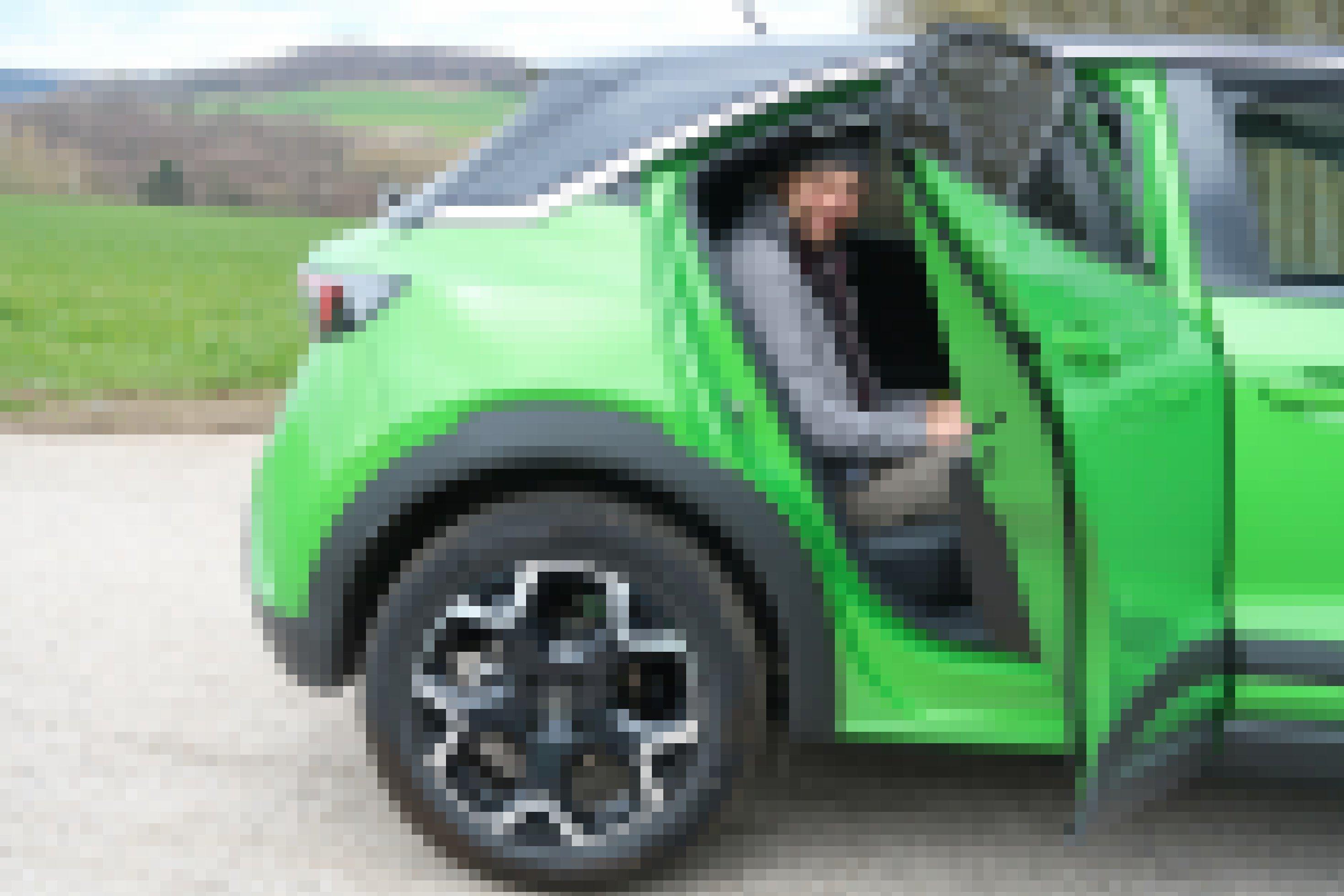 Ein Mann mit Mütze sitzt auf der Rückbank eines Kleinwagens. Die Tür ist geöffnet.