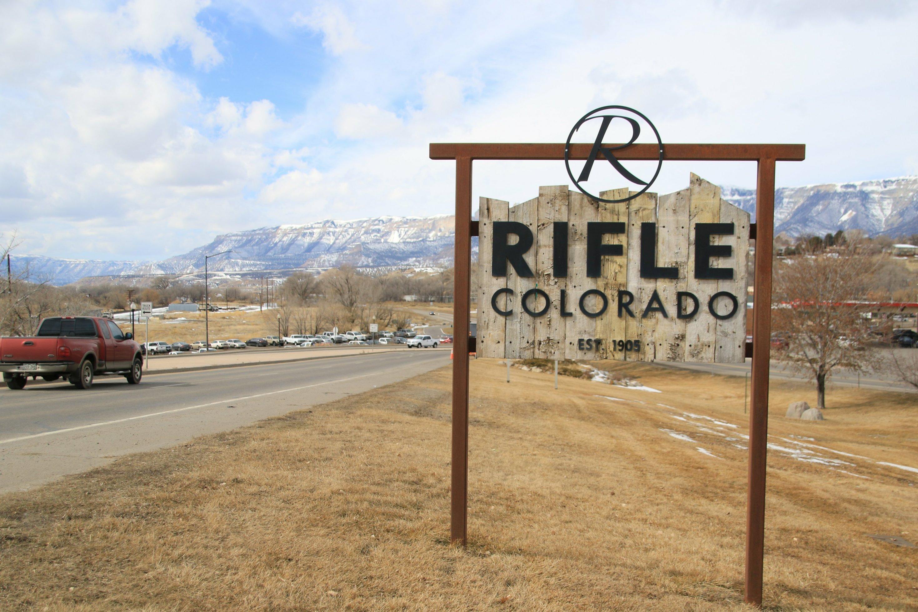 """Ein hölzernes Ortsschild an einer Straße. Aufschrift: """"Rifle""""."""