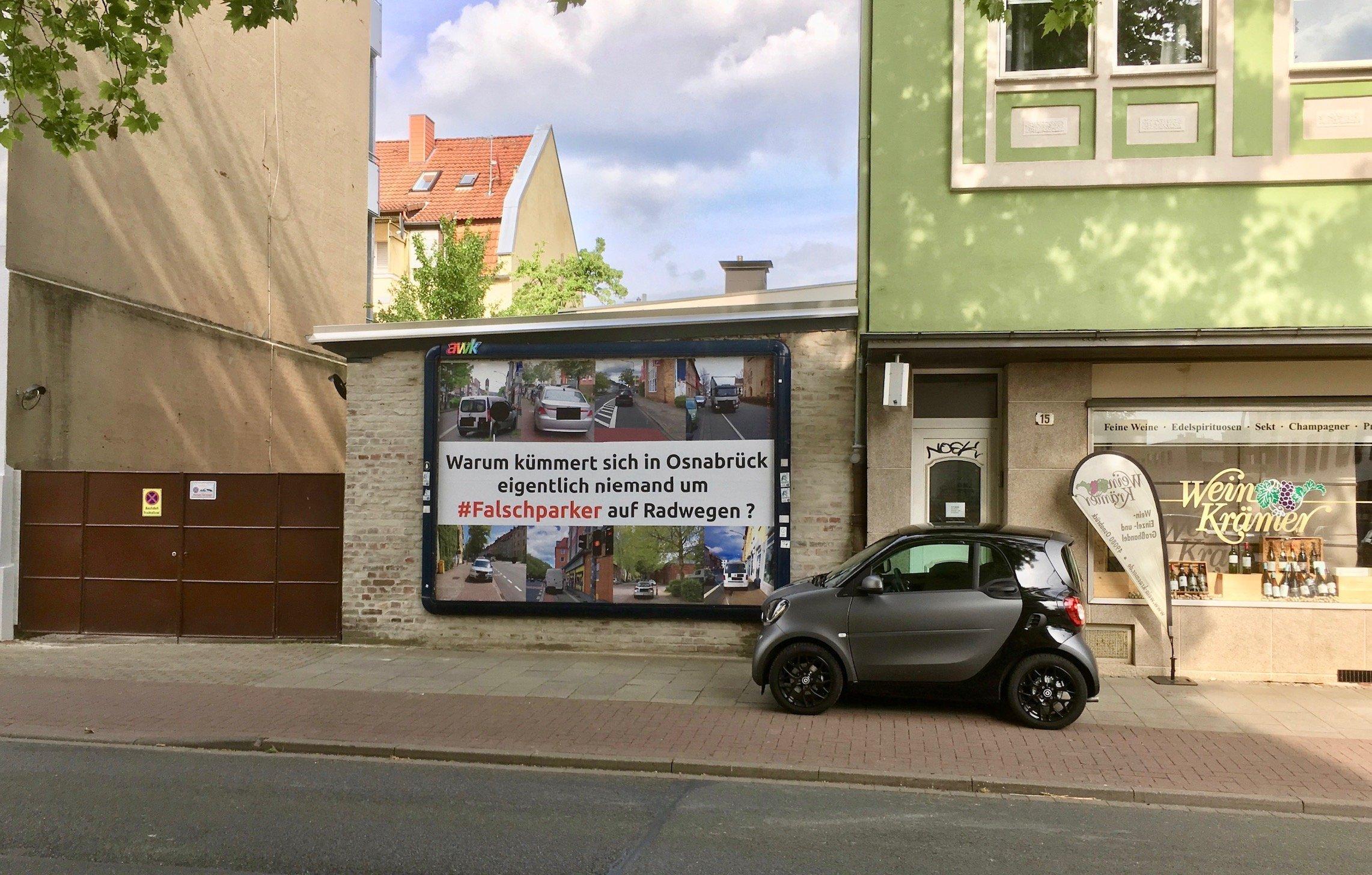 """Ein grau-schwarzfarbener Smart steht auf den Gehweg neben einem Radweg. Er steht direkt neben einer Plakatwerbung die Falschparker mit der Aufschrift:"""" Warum kümmert sich in Osnabrück eigentlich niemand um #Falschparker auf Radwegen?"""""""