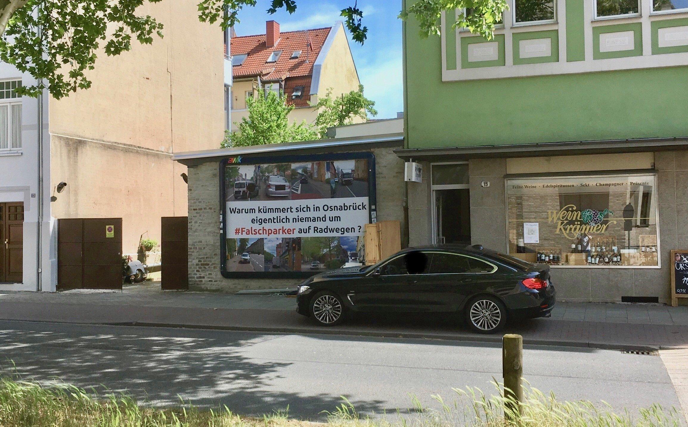 Eine dunkle Limousine steht vor dem Falschparker-Werbeplakat auf dem Radweg.