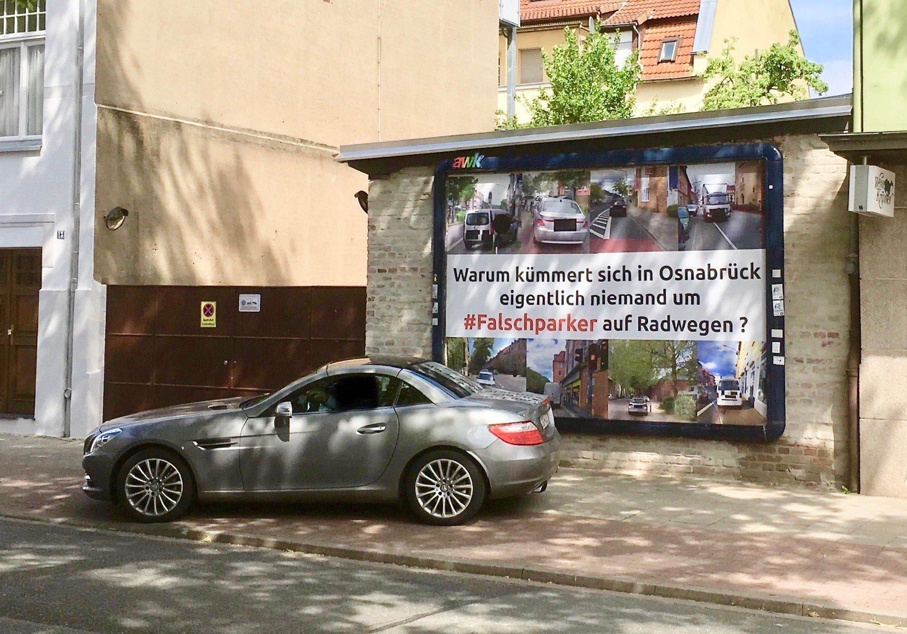 """Ein Sportwagen von BMW steht quer auf dem Rad und Fußweg. Es steht mit dem Heck vor dem Plakat mit dem Schriftzug """"Warum kümmert sich in Osnabrück eigentlich niemand um #Falschparker auf Radwegen?"""""""