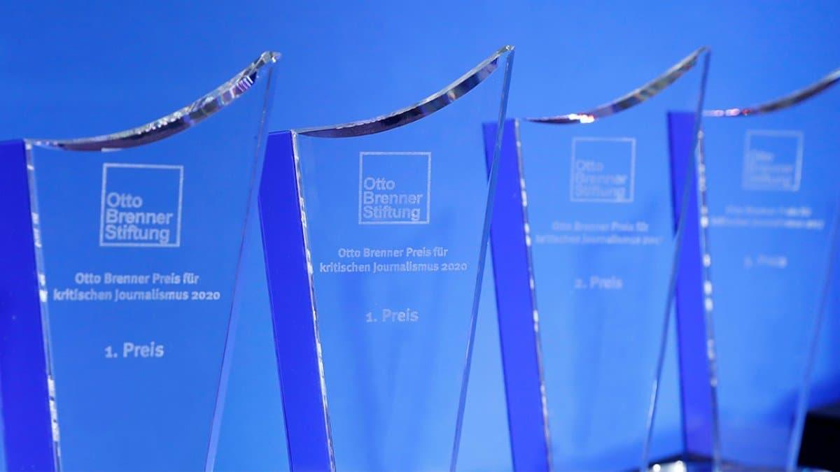 Mehrere Otto-Brenner-Preis-Trophäen aus Glas stehen vor einem blauen Hintergrund.