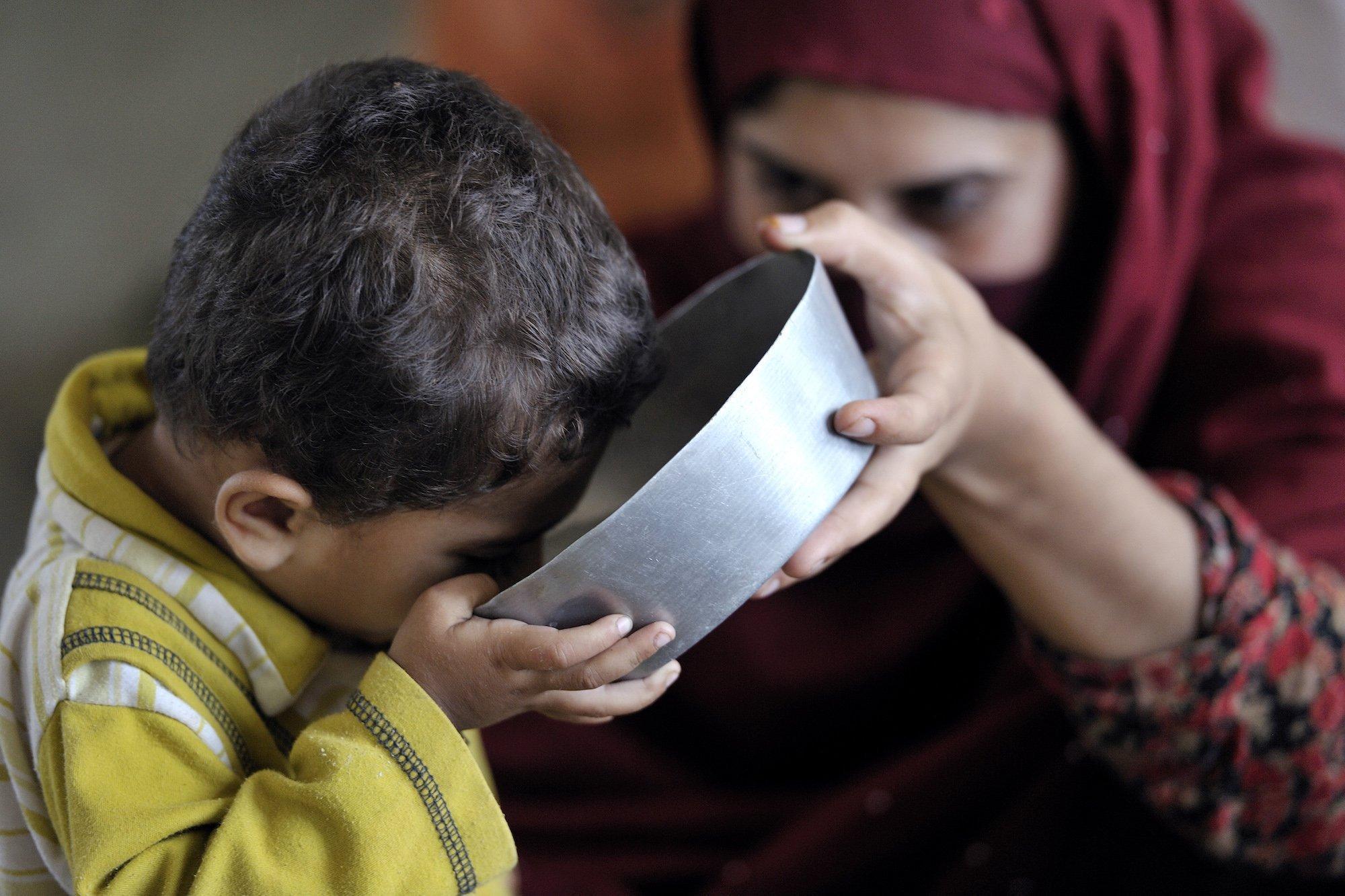 Ein kleines Kind trinkt aus einer Metallschüssel, im Hintergrund ist seine Mutter zu sehen, die das Gefäß hält. Viele Bewohner von überfluteten Orten in Pakistan mussten fliehen und fanden Schutz in Lagern und Versorgung von internationalen Unterstützern. Hier trinkt ein durstiges Kind sauberes Wasser, das UNICEF-Helfer bereitgestellt haben.