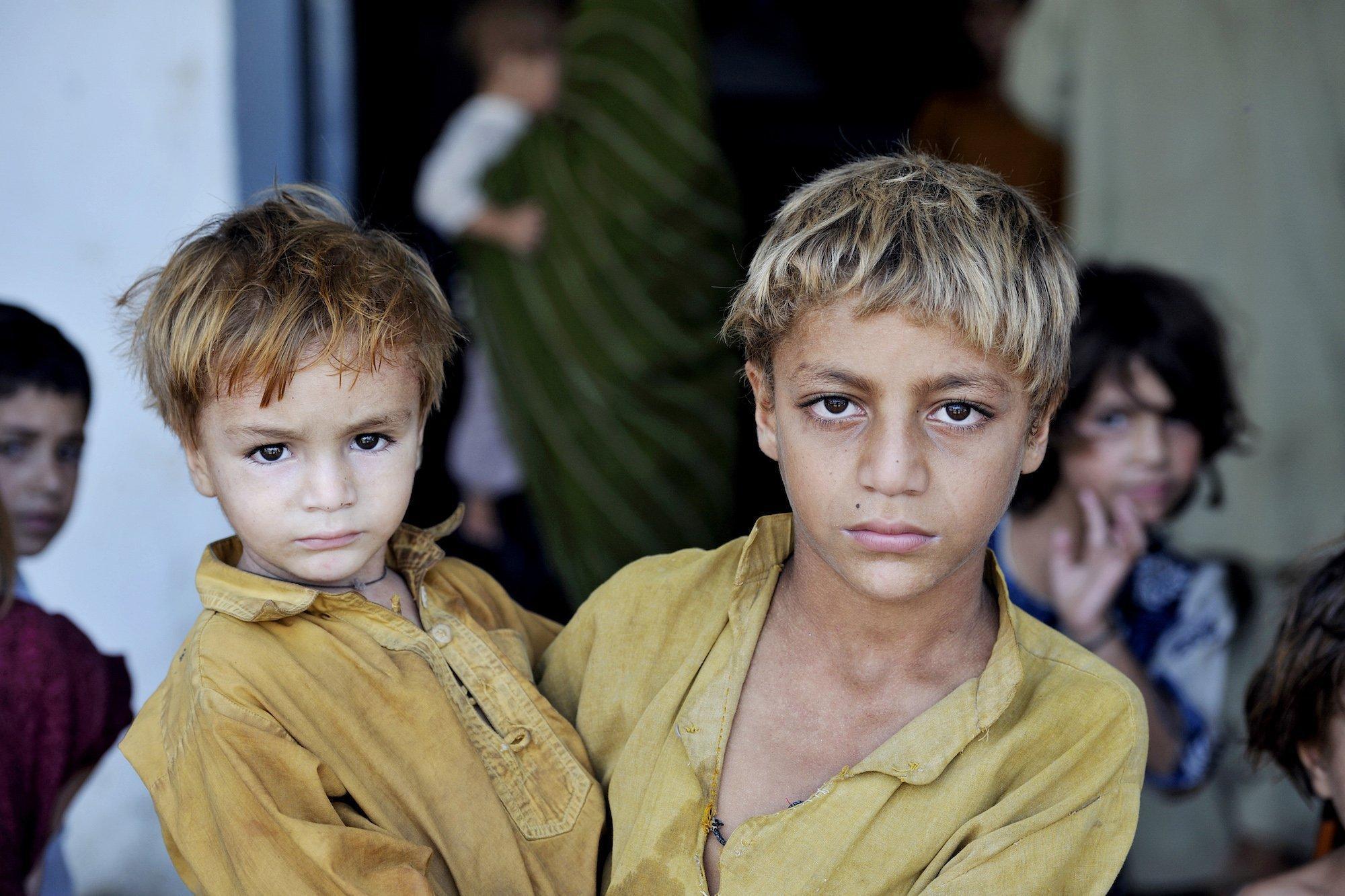Ein älterer Junger hält seinen jüngeren Bruder auf dem Arm, beide schauen ernst in die Kamera. Dieses Bruderpaar fand damals – wie Tausende andere – Zuflucht in einer Schule des Charsadra-Distrikts in der nordwestlichen Grenzprovinz Khyber Pakhtunkhwa.