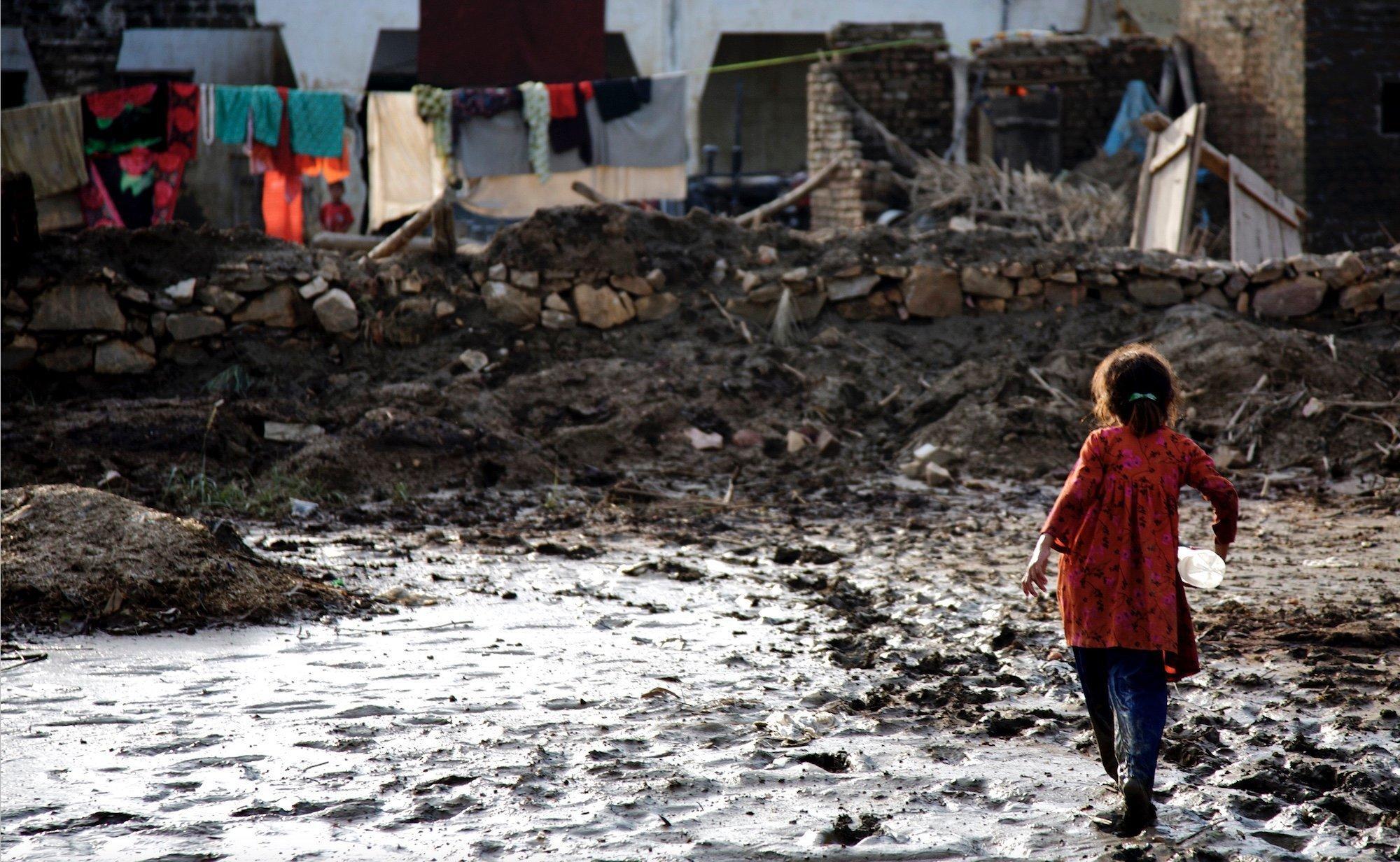 Ein Mädchen mit einer Plastik-Wasserflasche unter dem Arm läuft an einer matschigen Pfütze entlang, die von einer zurückgehenden Überschwemmung zurückgeblieben ist.
