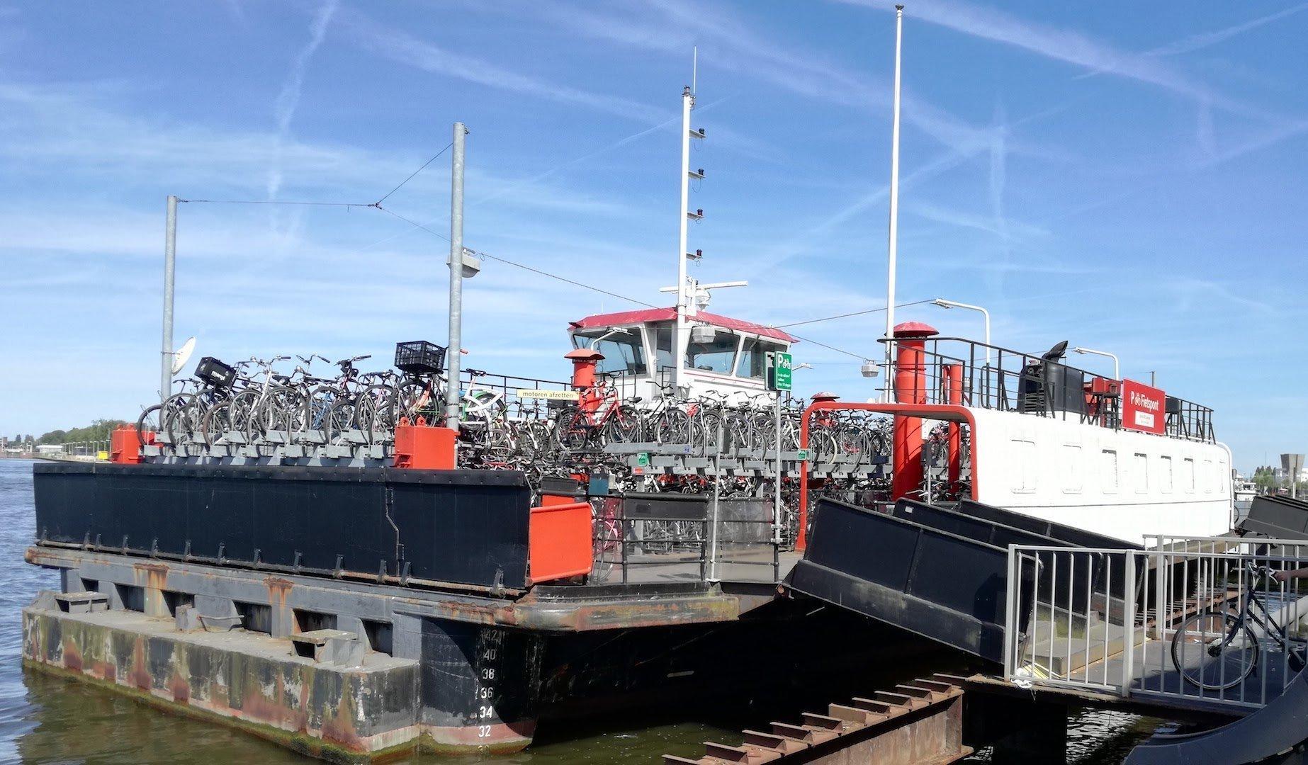 Am Hafen dockt ein Schiff an, das beladen mit Fahrrädern ist.