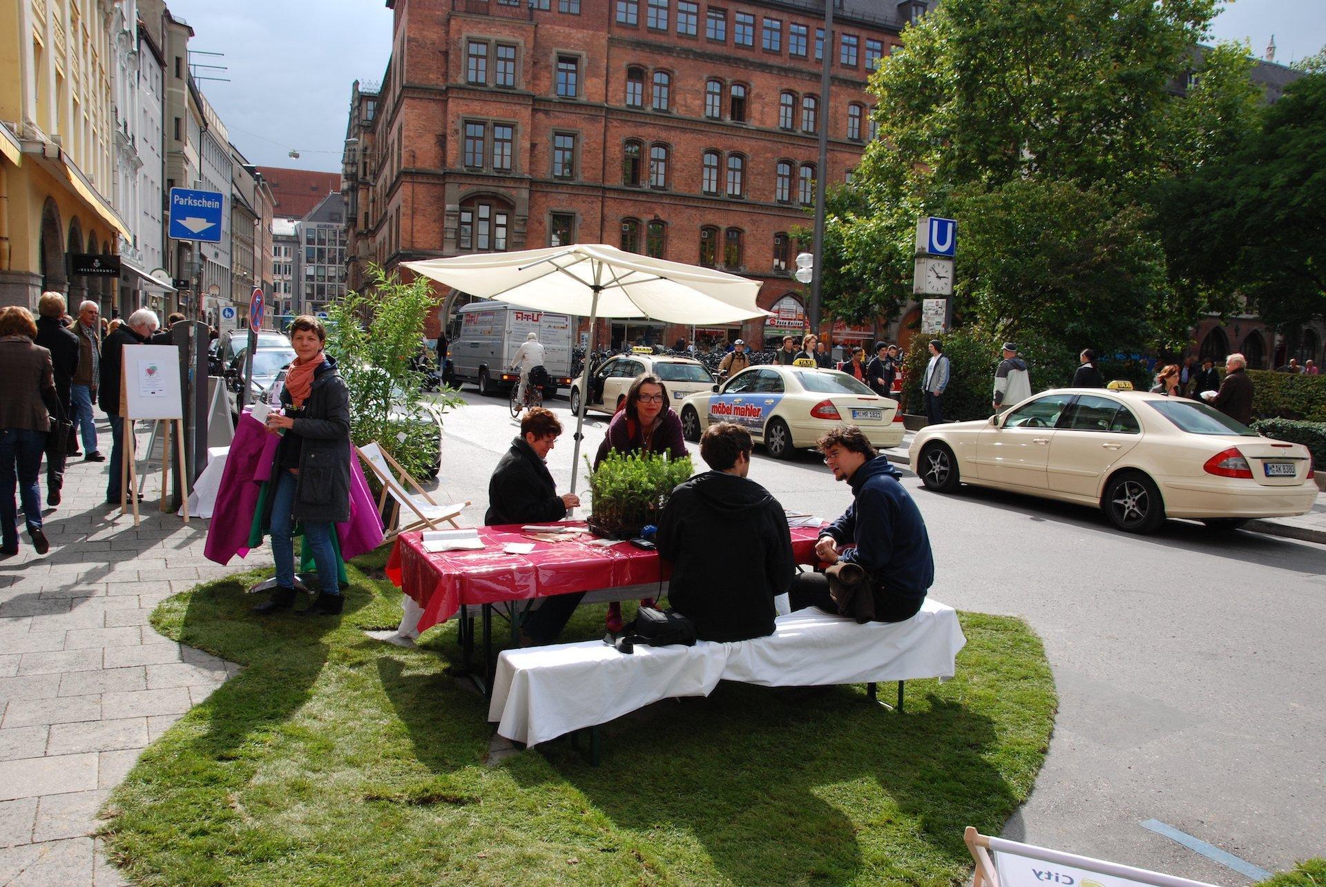 Die Aktivisten haben Rasen als Riesenherz zugeschnitten und eine Biergarnitur nebst Sonnenschirm aufgestellt