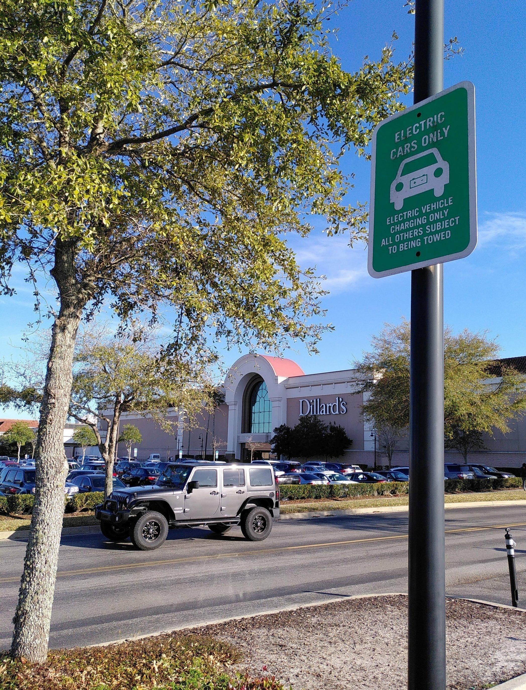 """Ein Parkplatz. Im Vordergrund ist ein Schild zu sehen, auf dem steht: """"Electric cars only""""."""