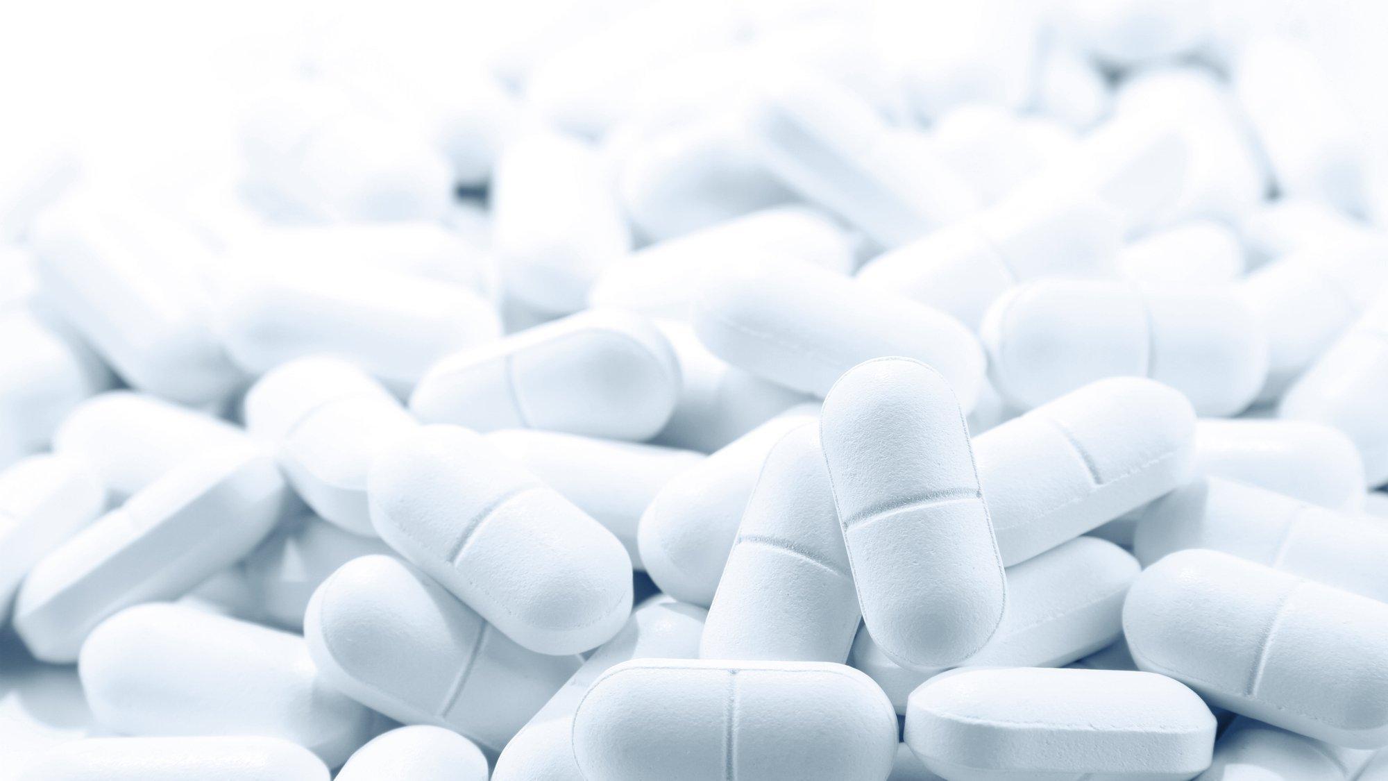 Das Bild zeigt eine große Zahl von weißen Tabletten auf einem Haufen. Das soll symbolisieren, dass es bisher keinen Wirkstoff gibt, aber mit Hochdruck nach ihm gesucht wird.