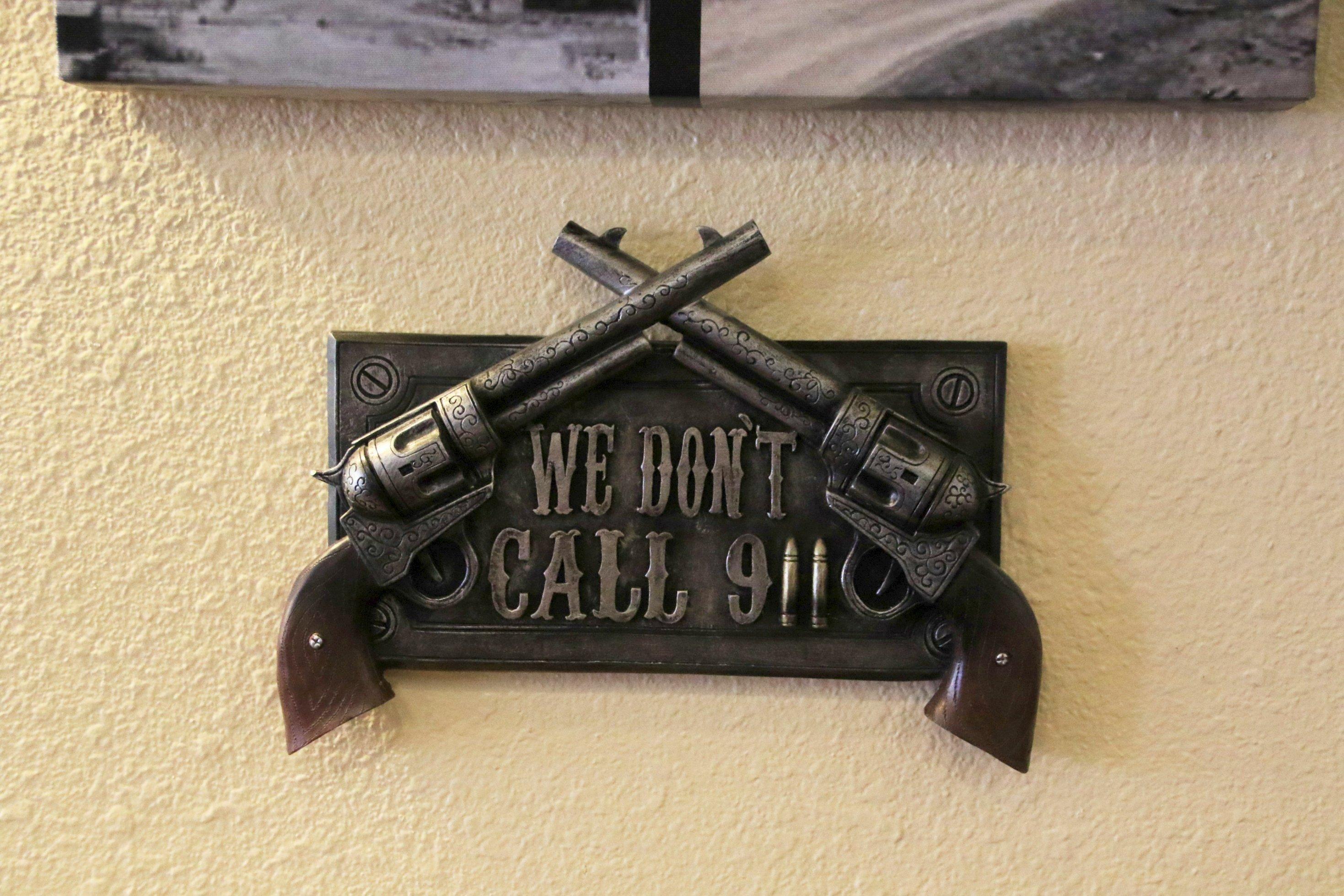 """Ein Messingschild mit Pistole und Aufschrift: """"We don't call 911."""""""