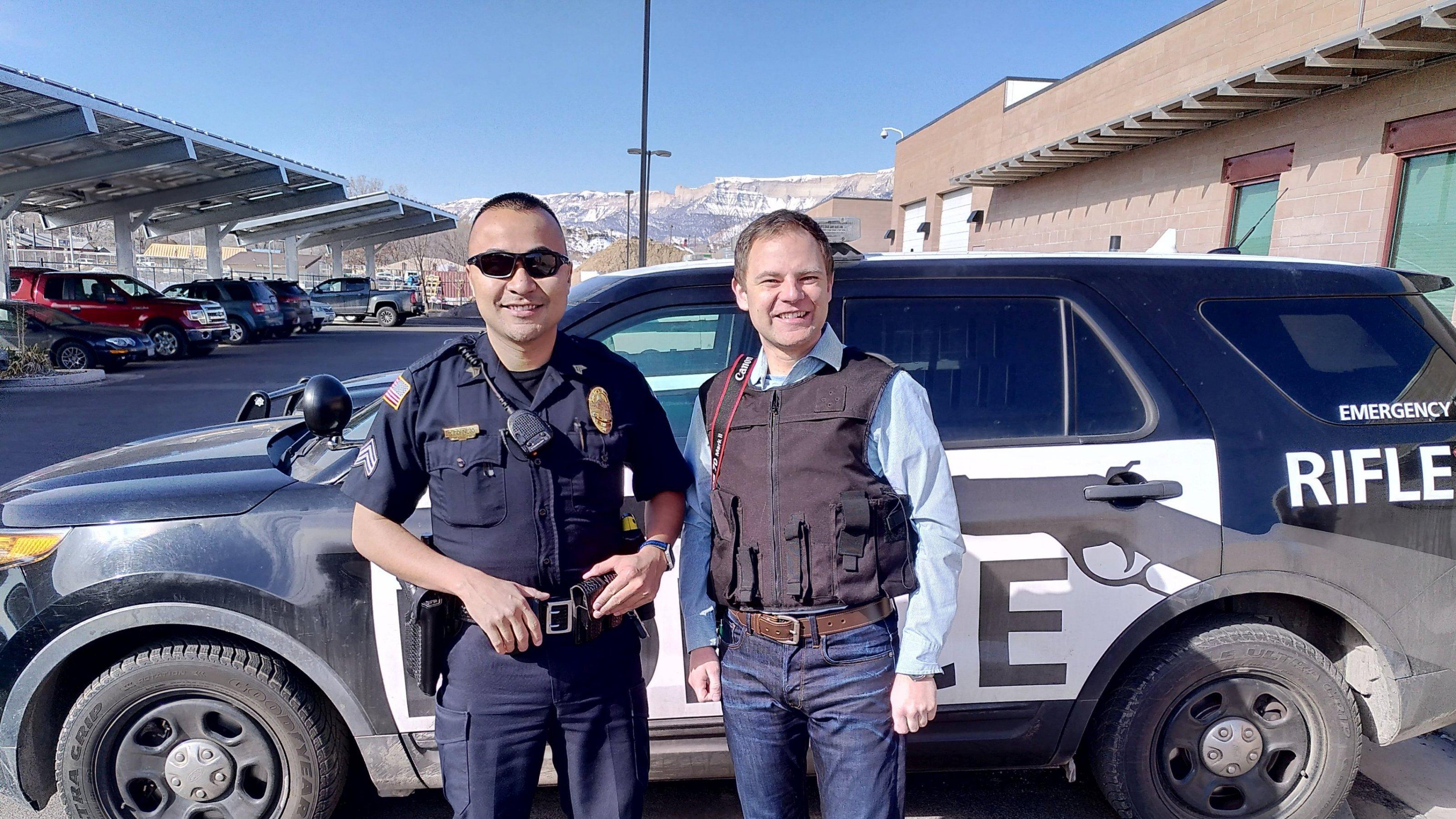 Ein uniformierter Polizist und ein Reporter mit kugelsicherer Weste stehen vor einem Einsatzwagen der Polizei.