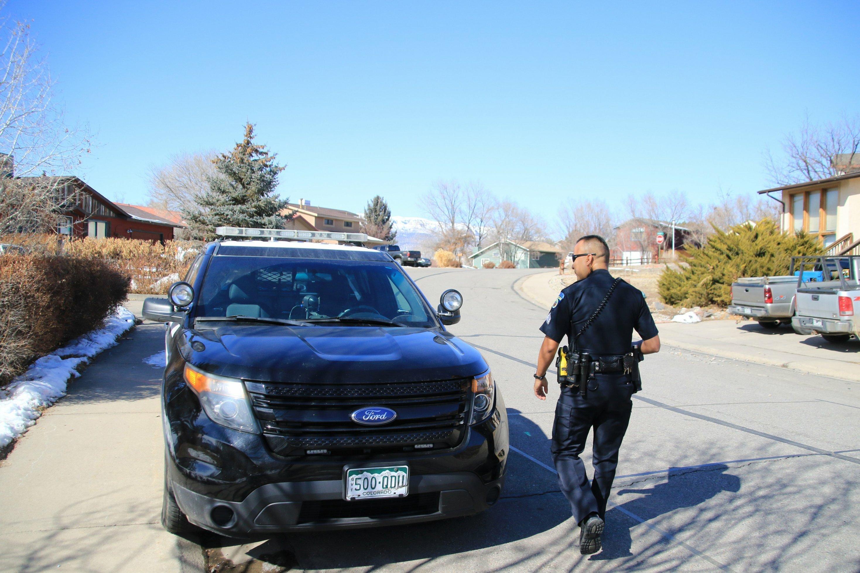Ein Polizist geht zu seinem Streifenwagen.
