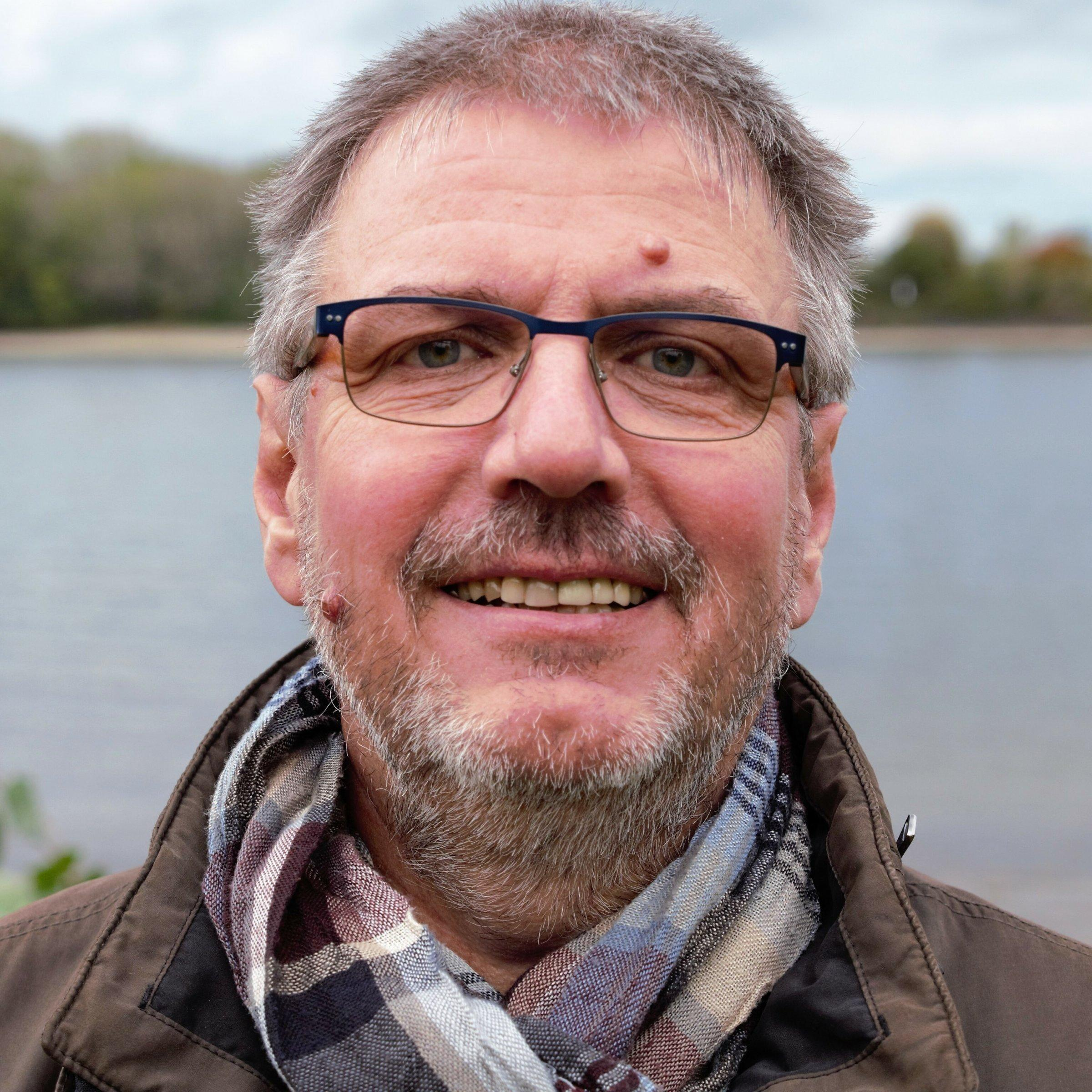 Grauhaariger Mann mit Brille, Schal und brauner Jacke blickt zum Betrachter, im unscharfen Hintergrund fließt der Fluss Rhein unter grau bewölkten Himmel.