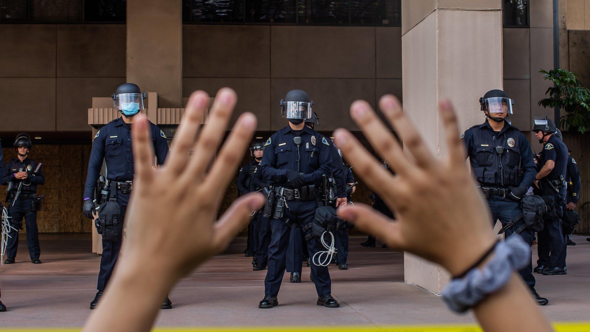 Ein Demonstrant hält seine Hände nach oben, während im Hintergrund Polizisten in Schutzausrüstung zu sehen sind.